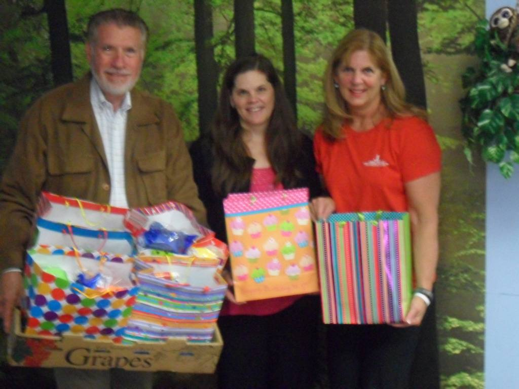 (From left)HSP co-founder Floyd Kettering, HSP Assistant Executive Director Kristin Maxwell, and Junior League member Sue Wilson with a few of the party kits for needy kids.