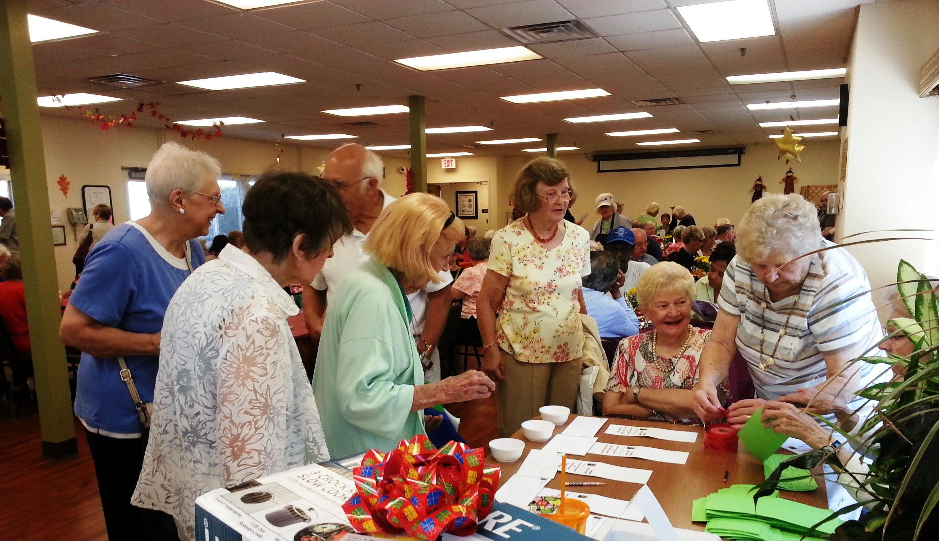 Visitors to the Palatine Township Senior Center Fall Festival visit the raffle table to register for prizes.
