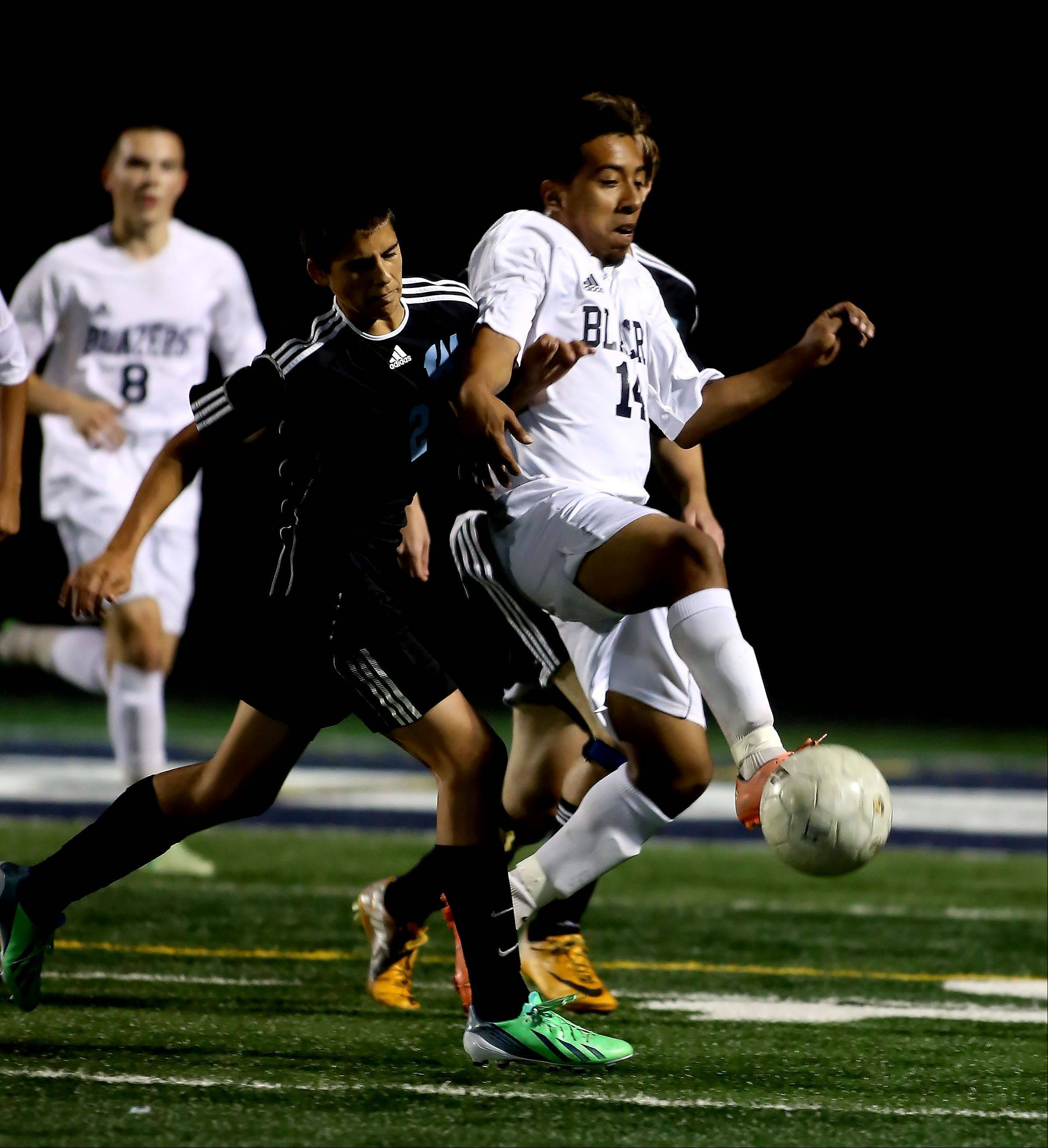Juan Amezquita of Addison Trail, right, takes control of the ball from Aaron Johnson, left, of Willowbrook in boys soccer action on Tuesday in Addison.