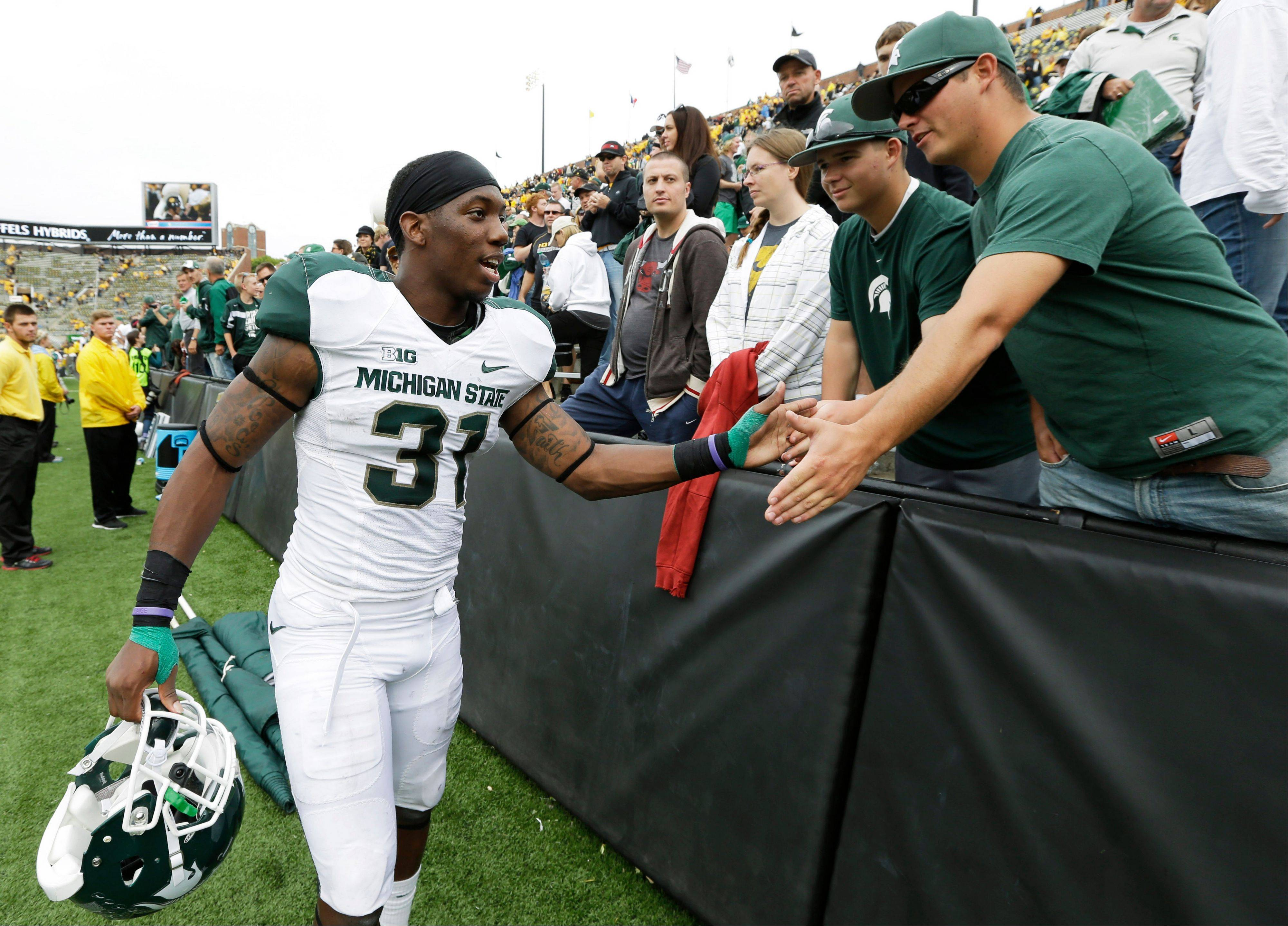 Michigan State cornerback Darqueze Dennard celebrates with fans after Saturday�s road win against Iowa.