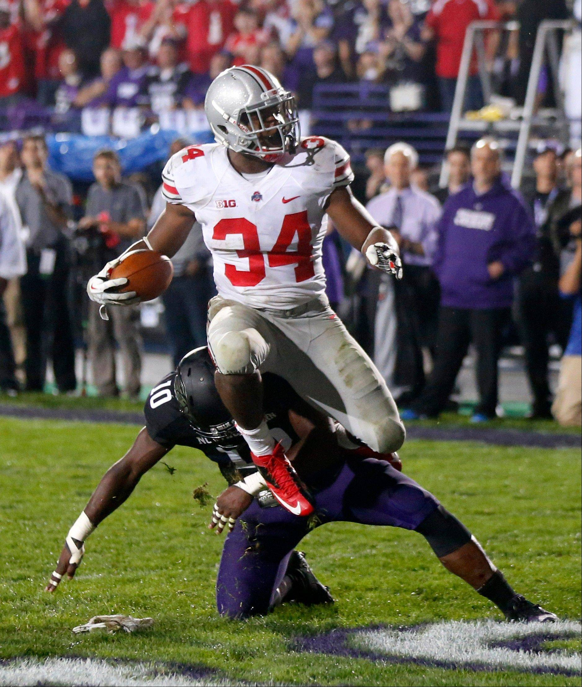 Ohio State running back Carlos Hyde scores over Northwestern safety Traveon Henry during the second half of Saturday�s game in Evanston. Hyde ran for three touchdowns in a 13�-minute span of the second half.
