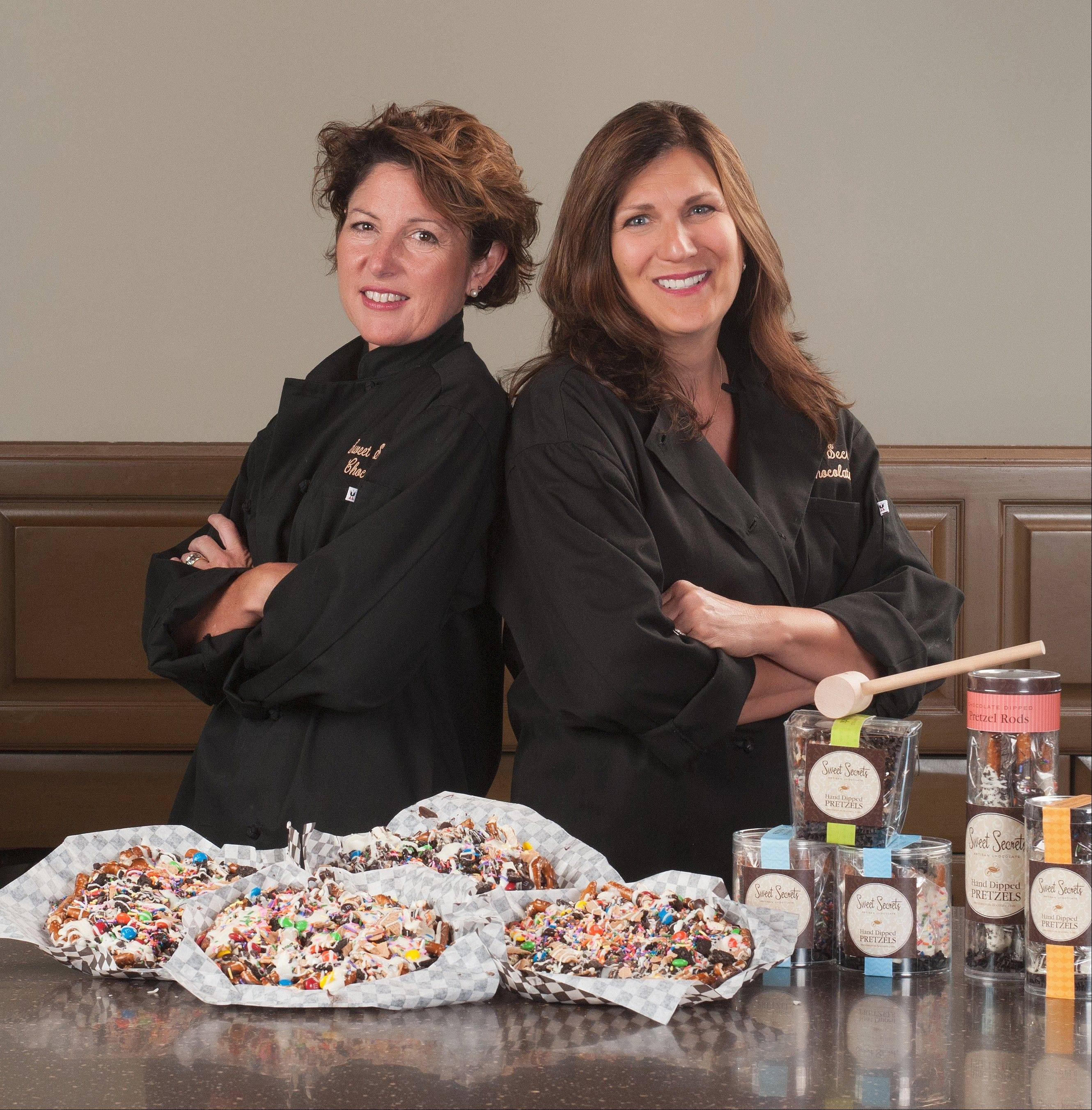 Chocolatiers Terri Kinney, left, and DeDe Barnicle, owners of Sweet Secrets Chocolates, were inspired by their children to create chocolate pretzel pizzas.