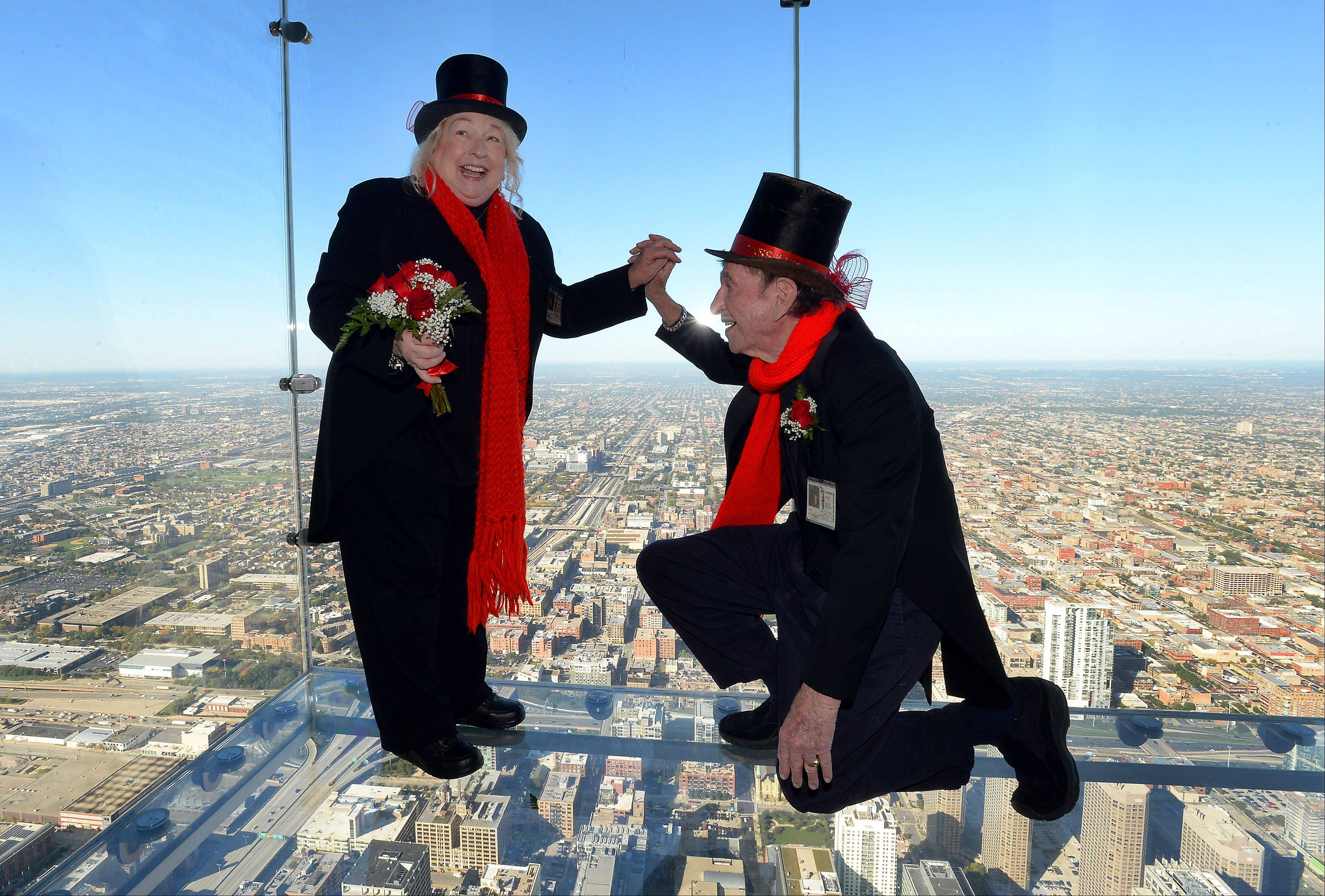 Still able to sweep each other off their feet after 35 years of marriage, Roselle chimney sweeps David and Dee Stoll renew their wedding vows from the Ledge of the Skydeck of the Willis Tower.