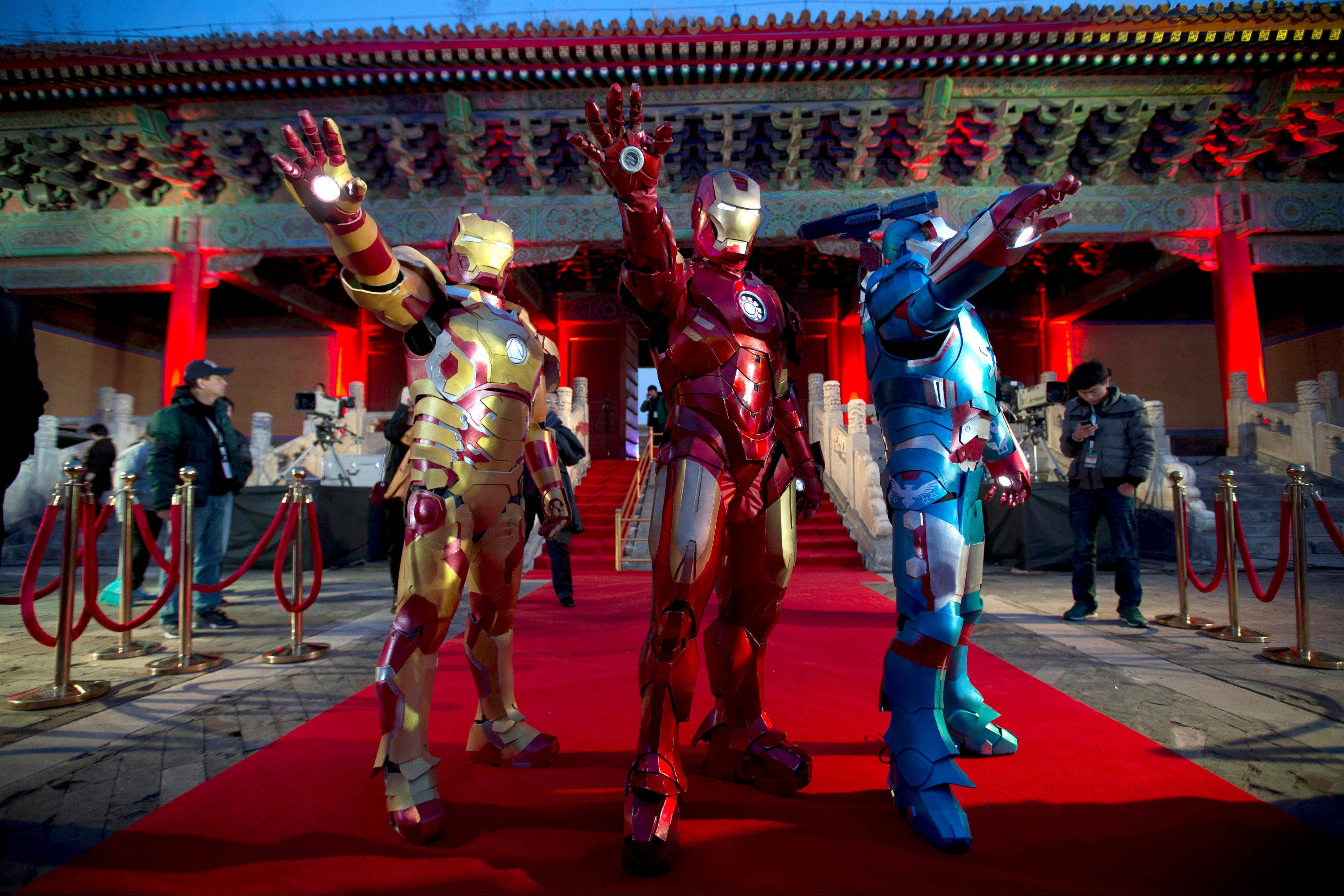 "In this Saturday, April 6, 2013 file photo, Chinese performers dressed as Iron Man pose for photos during a promotional event for the movie ""Iron Man 3"" before its release in China in early May at the Imperial Ancestral Temple in Beijing's Forbidden City. Hong Kong Disneyland is adding an Iron Man-themed area in the hopes that the Marvel superhero's success at the Chinese box office will help draw more visitors to the underachieving resort. The park said Tuesday, Oct. 8 that the Iron Man Experience is planned to open by late 2016."