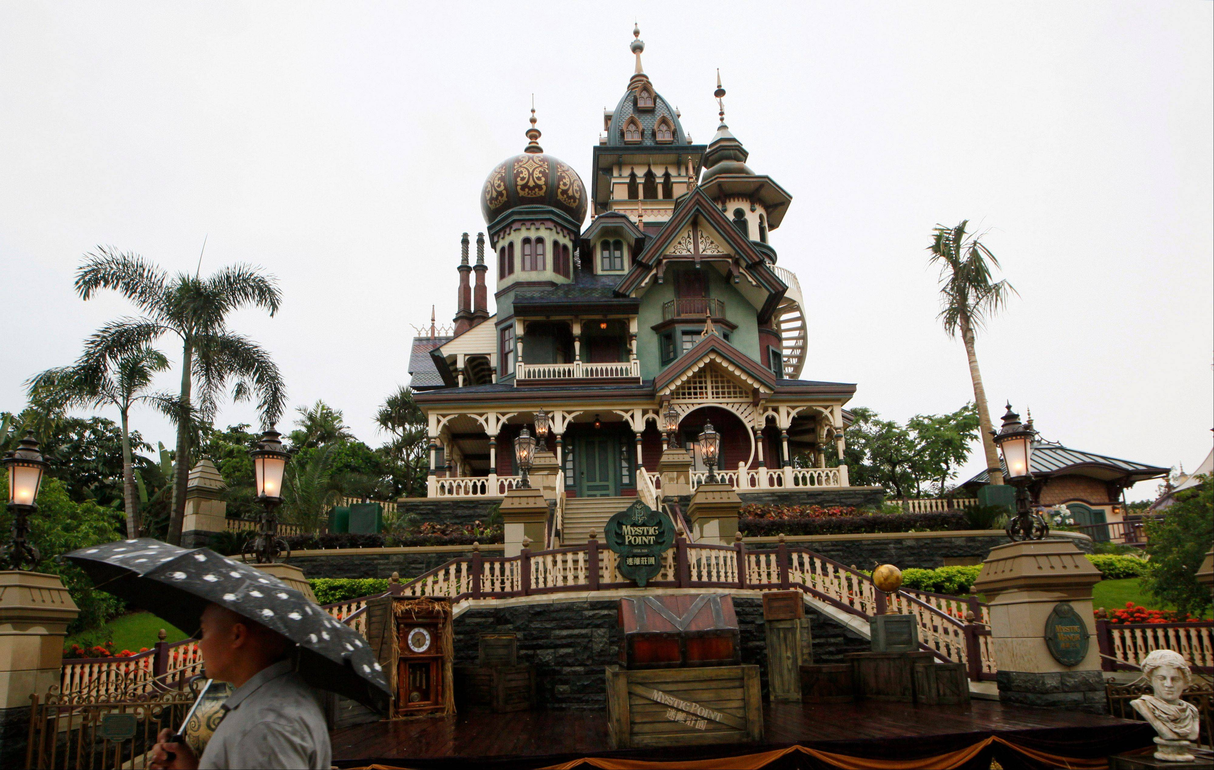 In this Thursday, May 16, 2013 file photo, a man walks past the Mystic Manor one day before the official opening for the public of the new attraction Mystic Manor at the Hong Kong Disneyland. Hong Kong Disneyland is adding an Iron Man-themed area in the hopes that the Marvel superhero's success at the Chinese box office will help draw more visitors to the underachieving resort. The park said Tuesday, Oct. 8 that the Iron Man Experience is planned to open by late 2016.