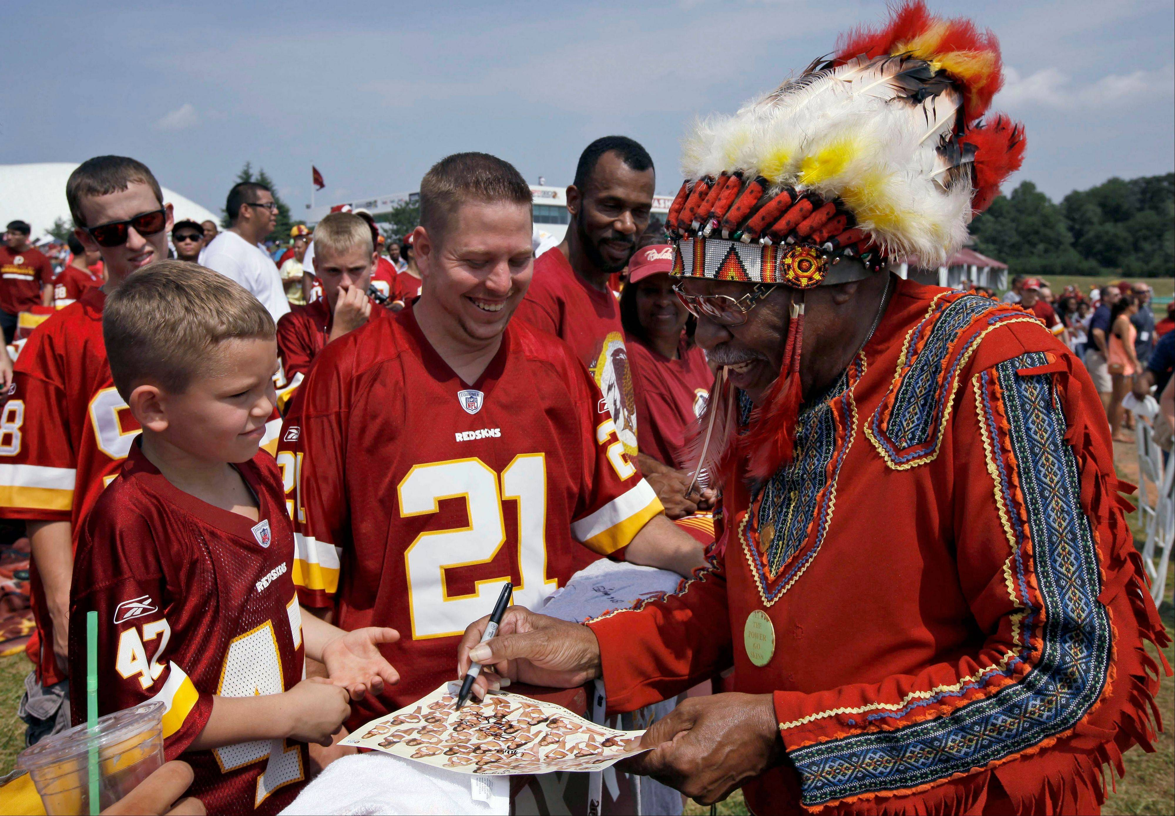 "Zena ""Chief Z"" Williams, unofficial mascot of the Washington Redskins, signs autographs during fan appreciation day at the Redskins' NFL football training camp in 2012."