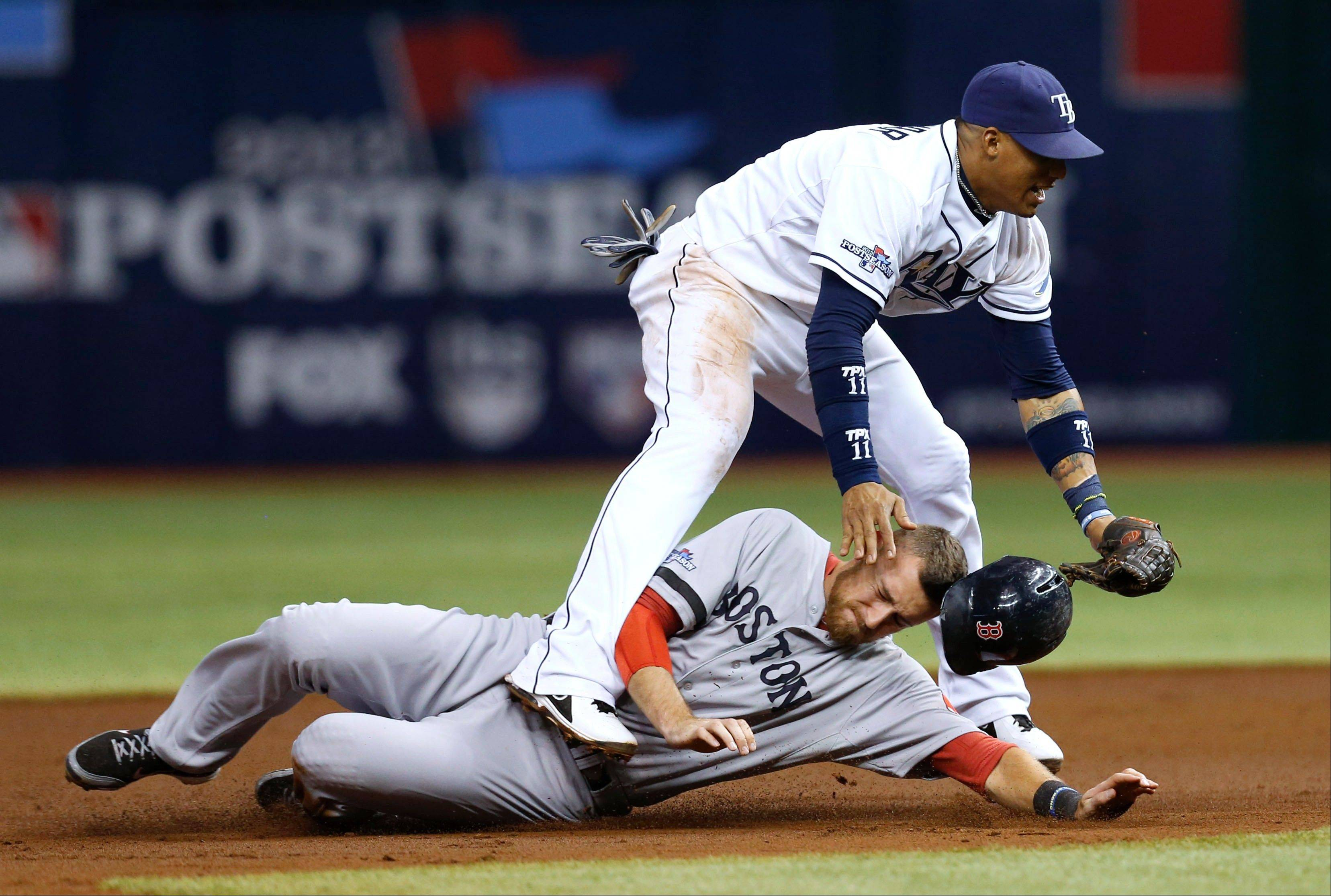 Boston's Will Middlebrooks slides under Tampa Bay Rays shortstop Yunel Escobar after he was tagged out on a double play in the third inning Tuesday in Game 4.