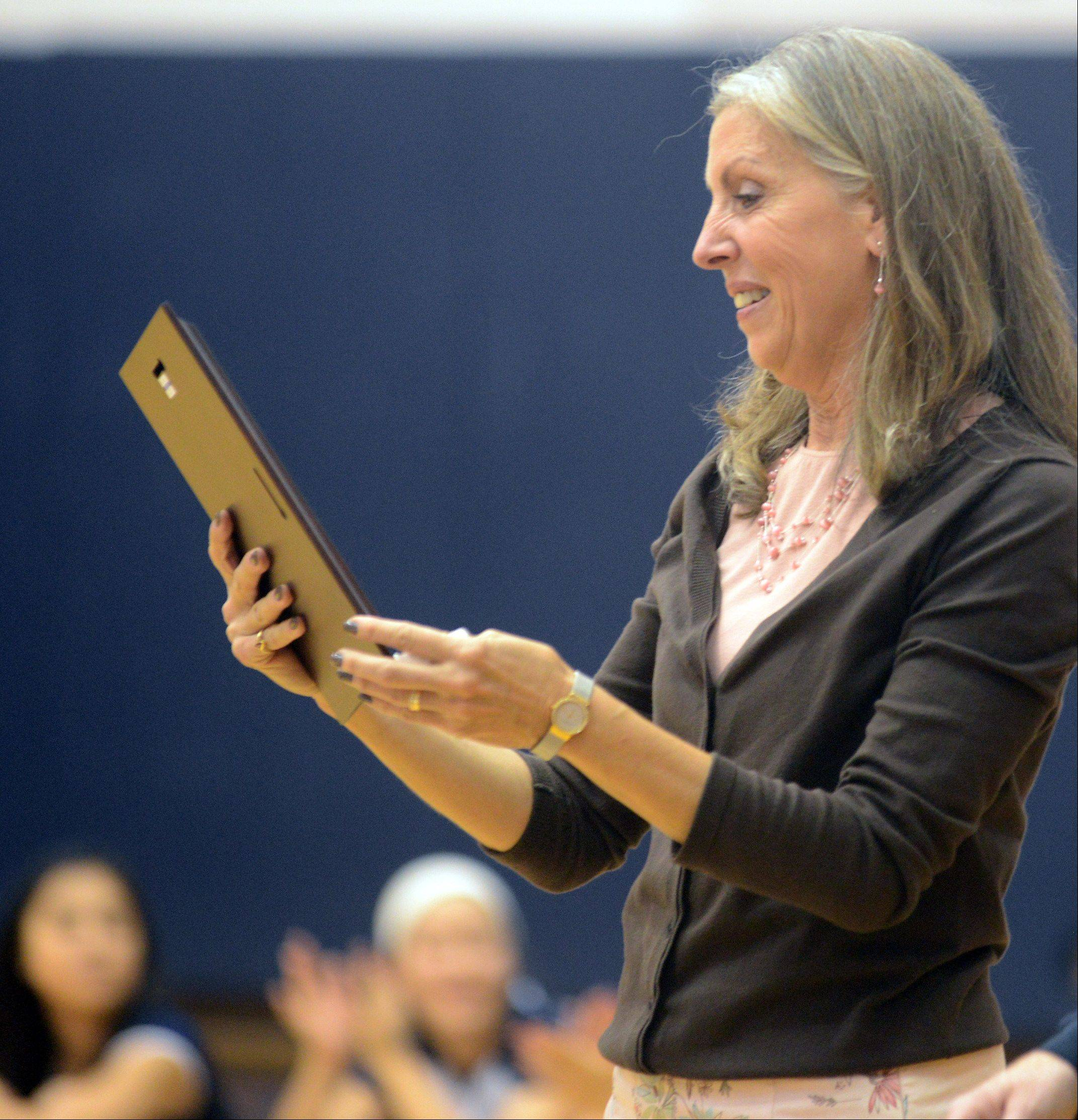 Conant volleyball coach Peggy Scholten was honored before a game with Schaumburg on Tuesday night at William N. Perry Gymnasium. Scholten is retiring after this, her 37th year of coaching. Here, Scholten admires a plaque given to her during a pregame tribute.