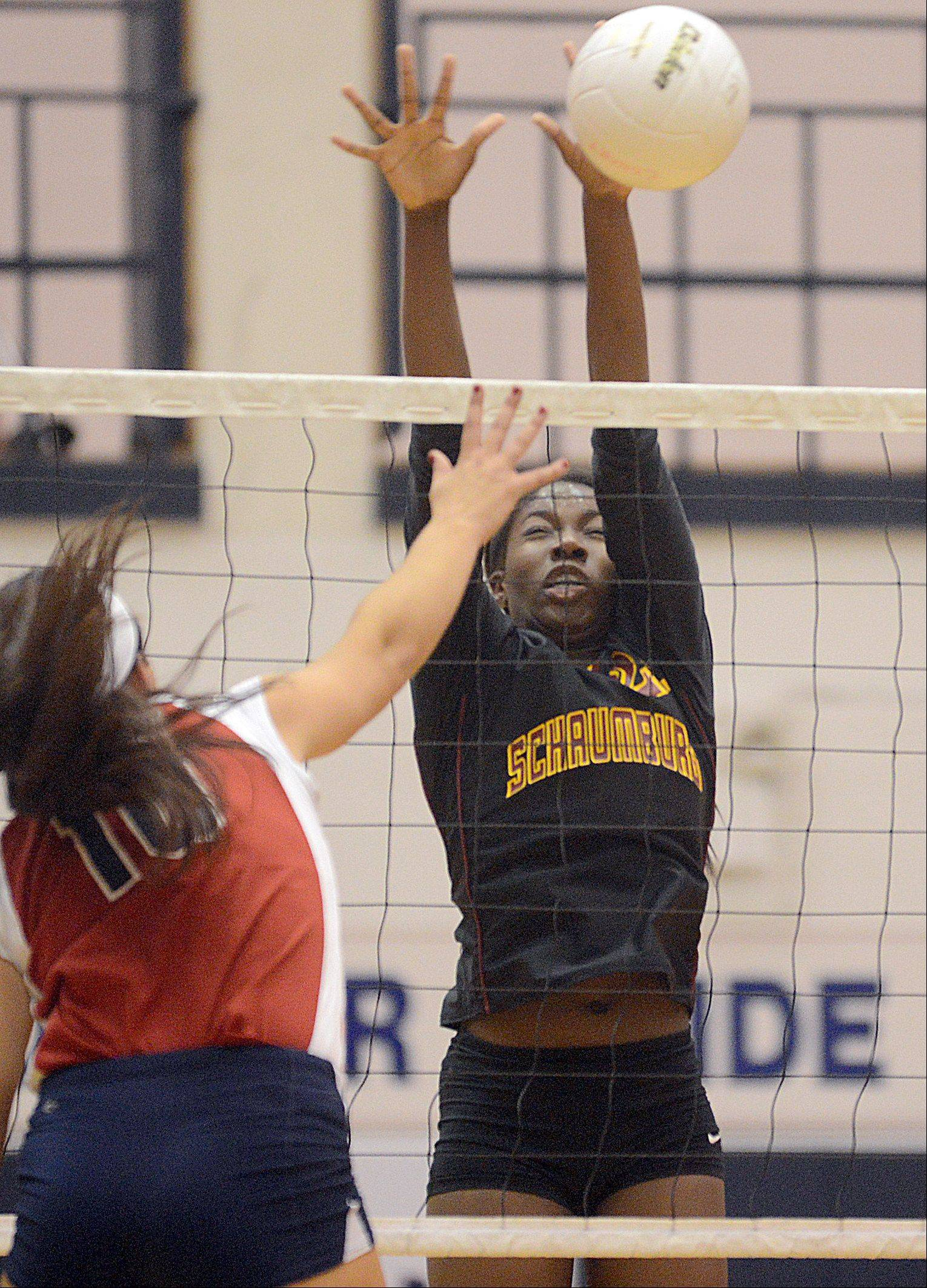 Conant's Alissa Wochal, left, tries to get the ball past Schaumburg's Oyinkan Akinola during varsity volleyball at Conant on Tuesday night.