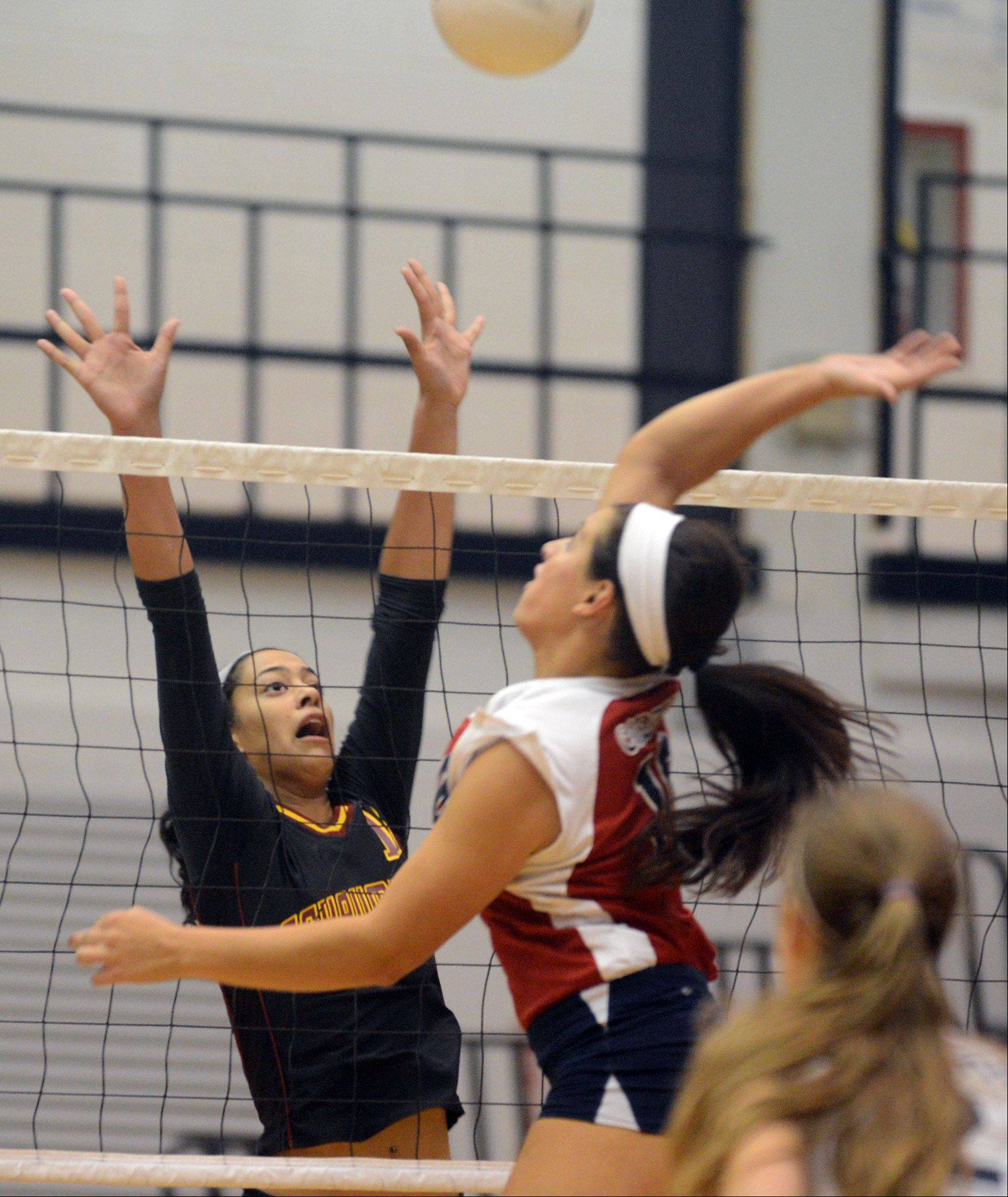 Conant's Alissa Wochal, right, tries to get the ball past Schaumburg's Kiana Lewis during varsity volleyball at Conant on Tuesday night.