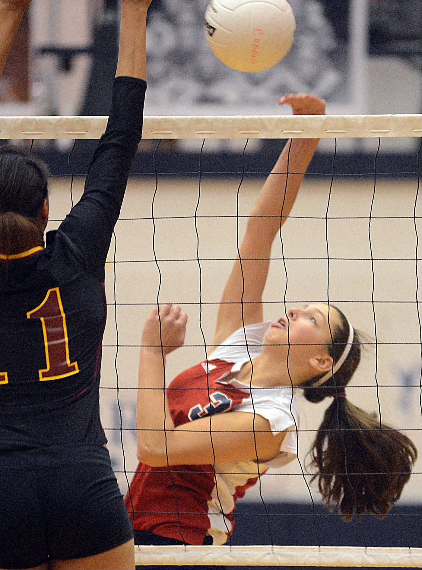 Conant's DeeDee Durr, right, tries to get the ball past Schaumburg's Jada Blackwell during varsity volleyball at Conant on Tuesday night.