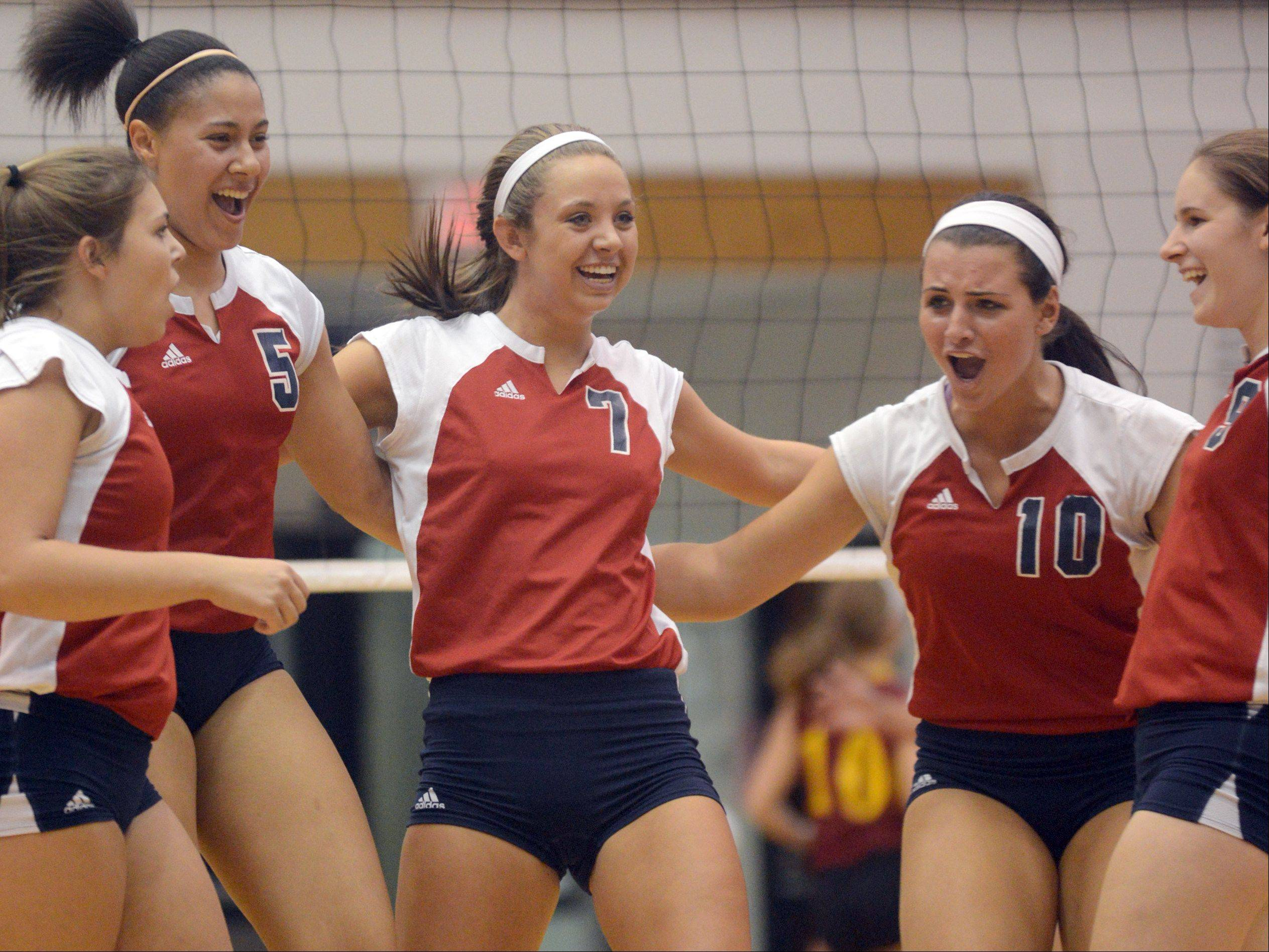Conant's players celebrate a point against Schaumburg during varsity volleyball at Conant on Tuesday night.