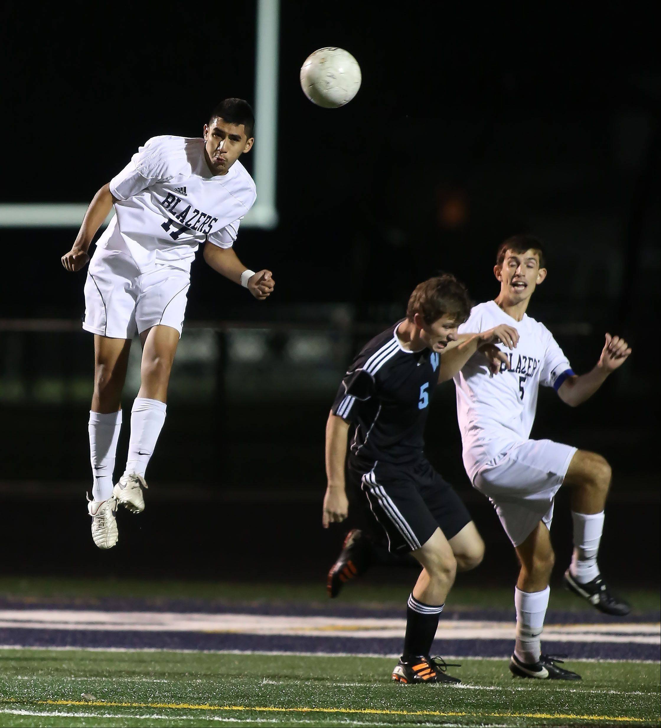 Sergio Marin of Addison Trail, left, heads the ball in boys soccer action against Willowbrook on Tuesday in Addison.