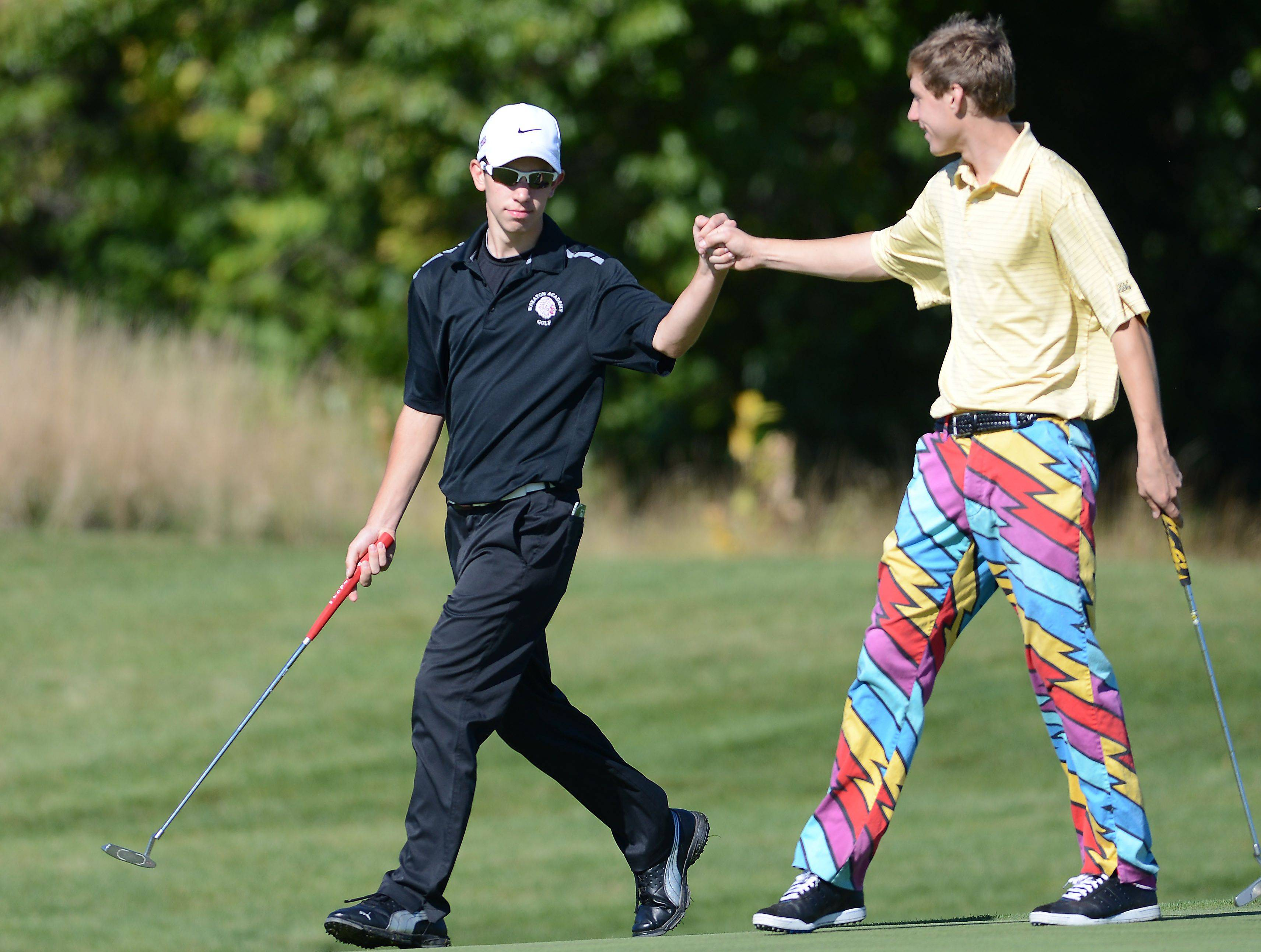 Wheaton Academy's Zack Spear, left, gets a fist bump from Aurora Central Catholic's Justin Prince after knocking in a 30+ foot putt on the first hole during Tuesday's regional golf action at Phillips Park in Aurora.