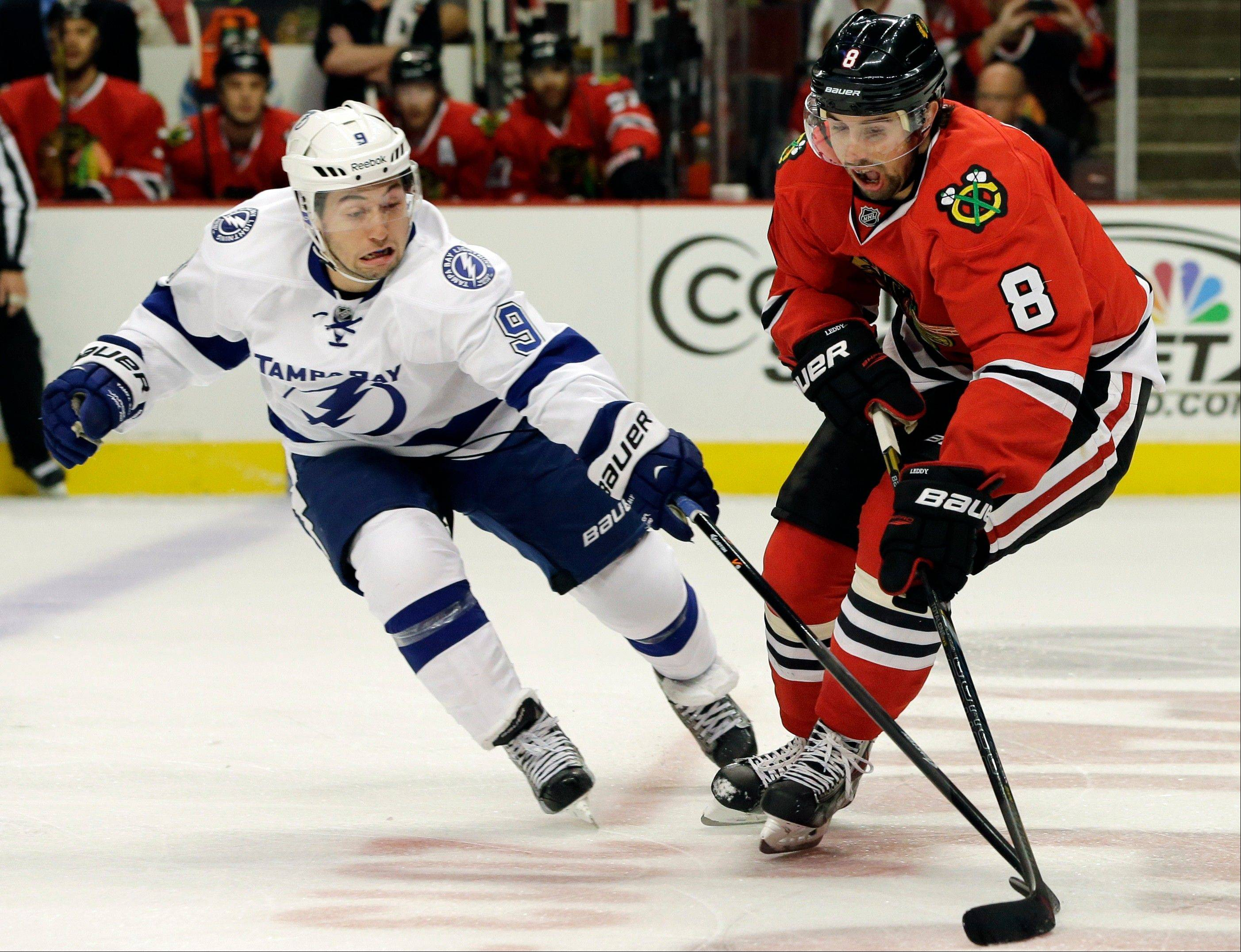Tampa Bay Lightning's Tyler Johnson, left, and Chicago Blackhawks' Nick Leddy (8) vie for the puck during the first period of an NHL hockey game in Chicago, Saturday, Oct. 5, 2013.