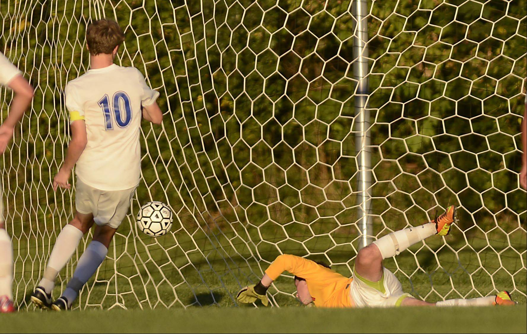 Dundee-Crown's Ben Stone scores the go-ahead, game-winning goal as Huntley goalkeeper Austen Emery dives for the ball Tuesday in Carpentersville.
