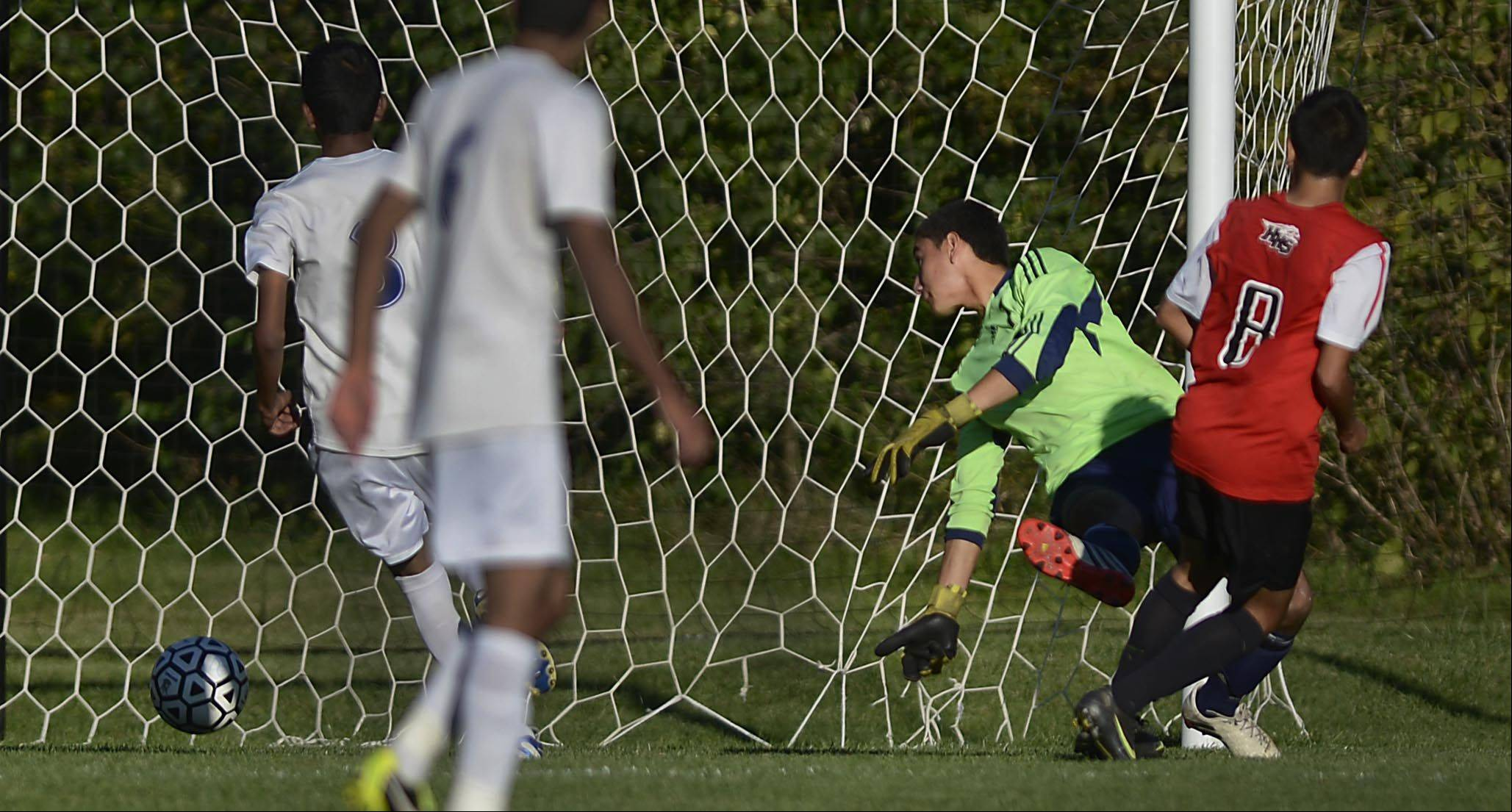 Huntley's Eduardo Gonzalez scores against Dundee-Crown goalkeeper Jose Gonzalez Tuesday in Carpentersville.