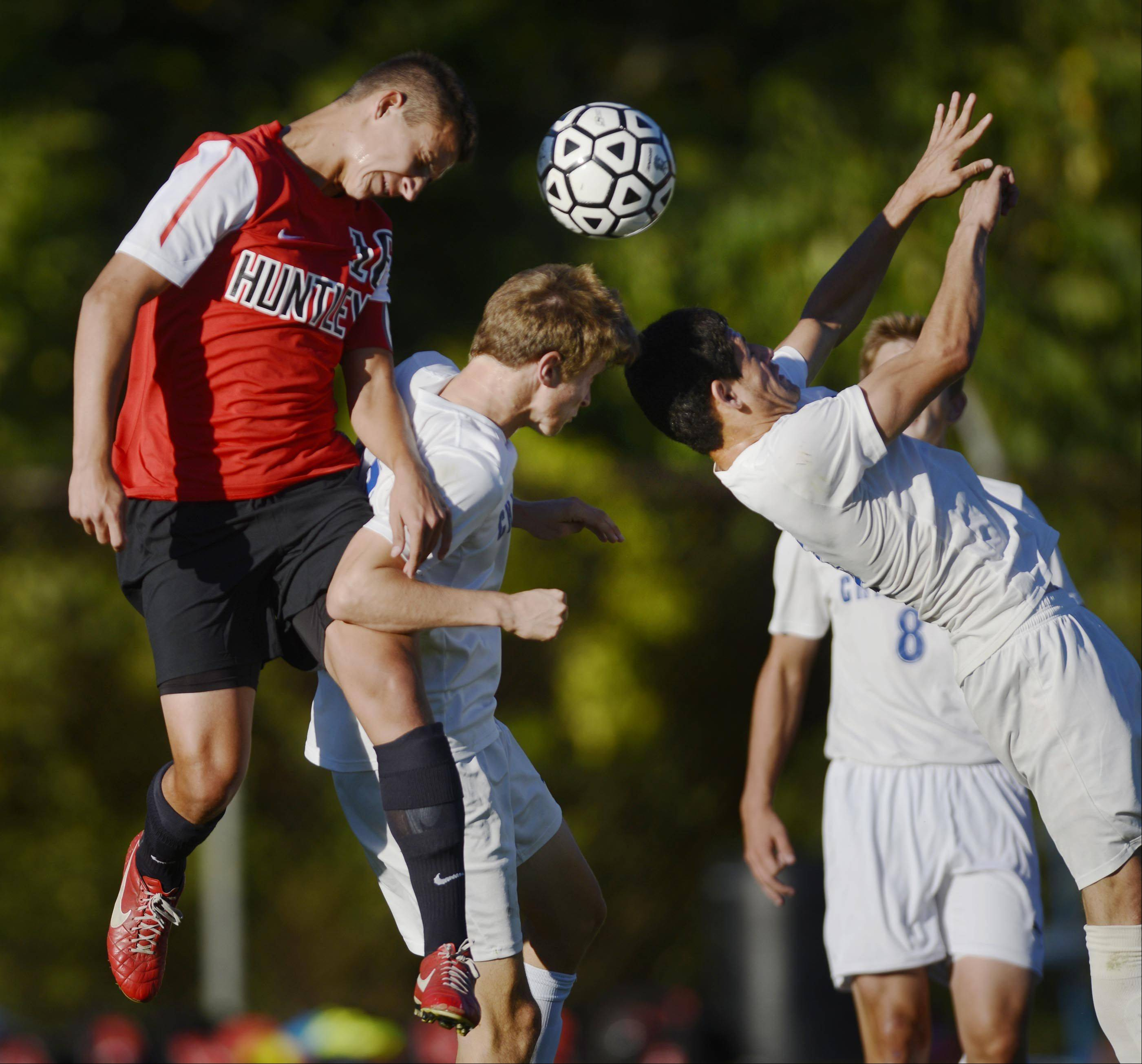 Huntley's Jakub Rys and Dundee-Crown's Ben Stone and Eduardo Arellano, right, compete for a header Tuesday in Carpentersville.