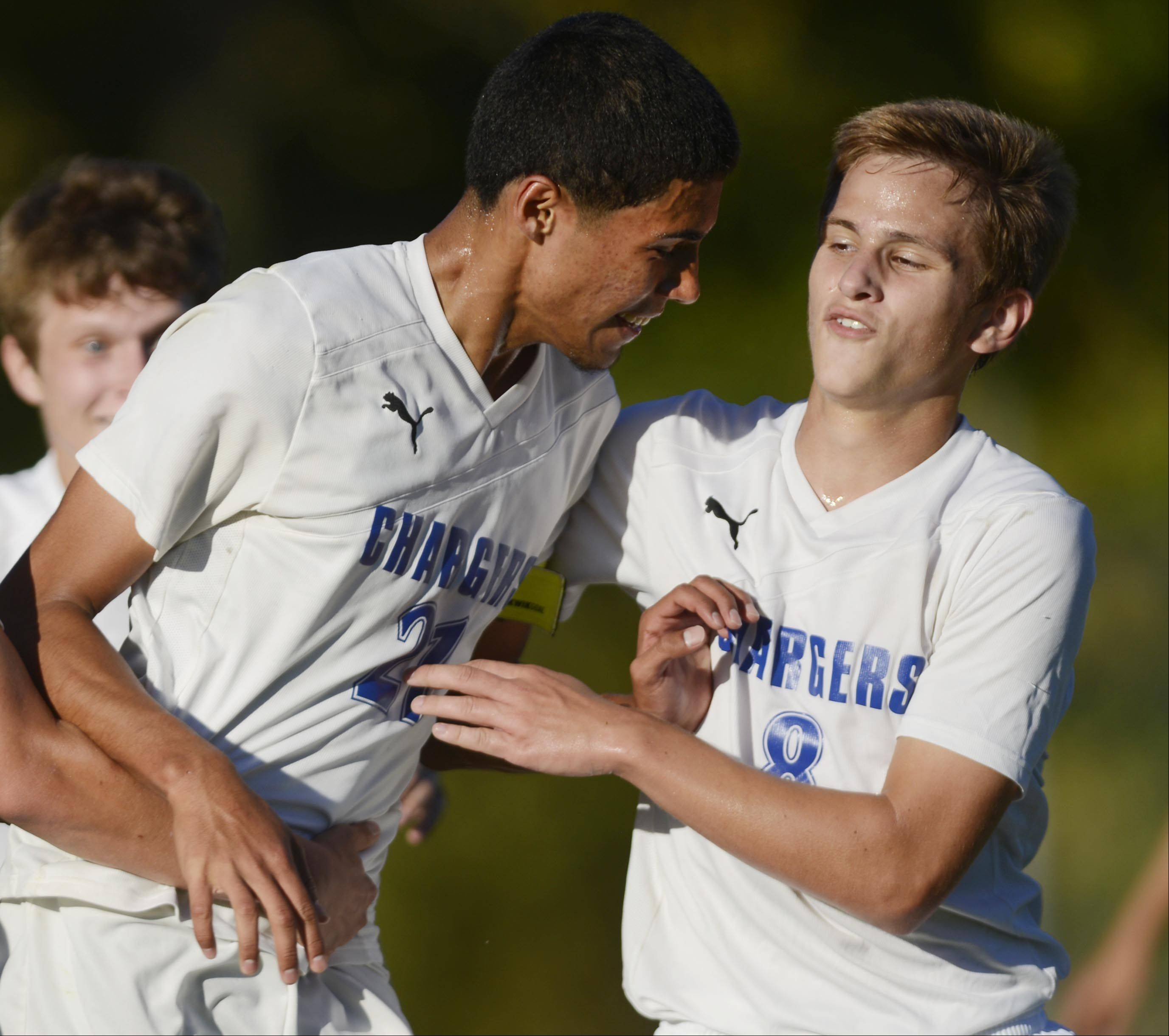 Dundee-Crown's Carlos Ramos is met by teammate Paul Buch after he scored the first Charger goal against Huntley Tuesday in Carpentersville.
