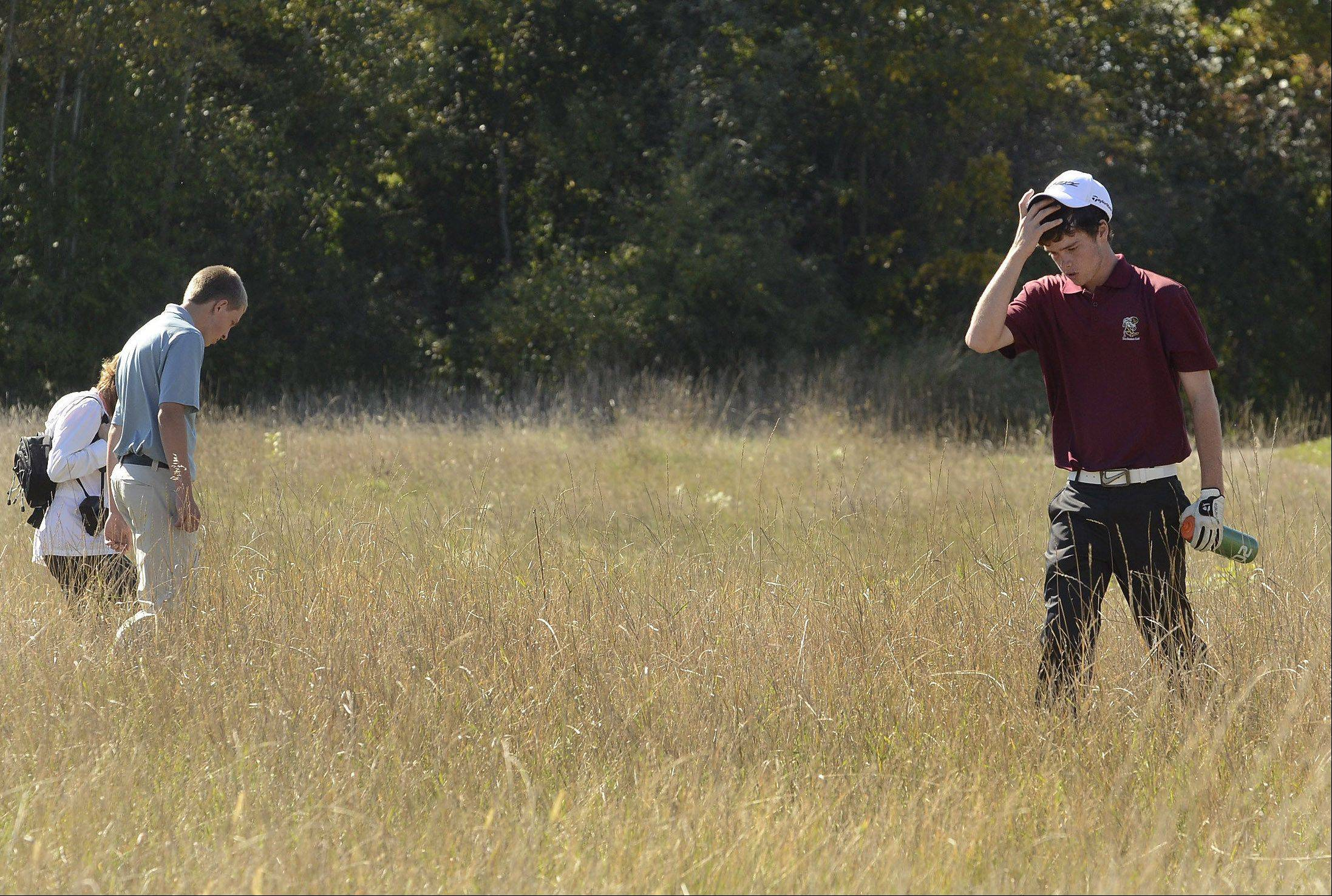 Jeremy Schwab, right, of Zion-Benton looks for his ball in the tall grass on 12, but couldn't find it costing him a stroke during the Class 3A Zion-Benton boys golf regional.