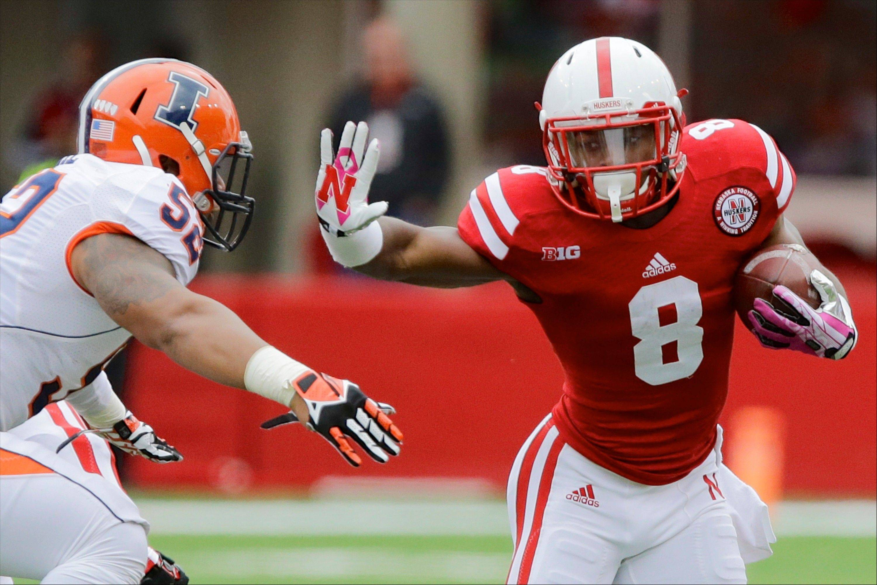 Nebraska's Ameer Abdullah runs past Illinois linebacker T.J. Neal in the second half of Saturday's game in Lincoln, Neb. Abdullah ran for a career-high 225 yards and two touchdowns in Nebraska's 39-19 win.