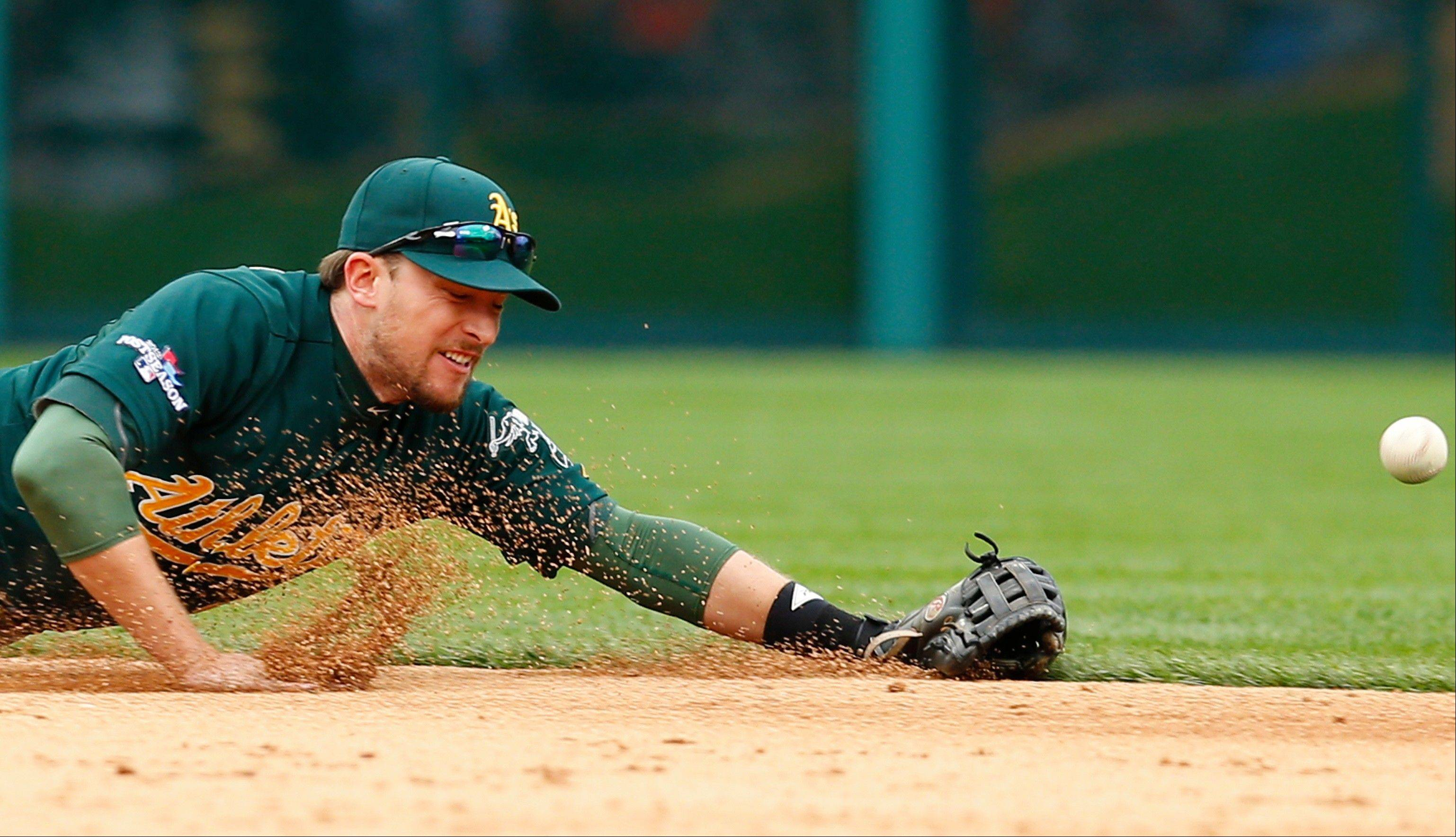 Athletics shortstop Jed Lowrie dives but is unable to stop the single by the Tigers' Prince Fielder during the sixth inning Monday in Detroit.