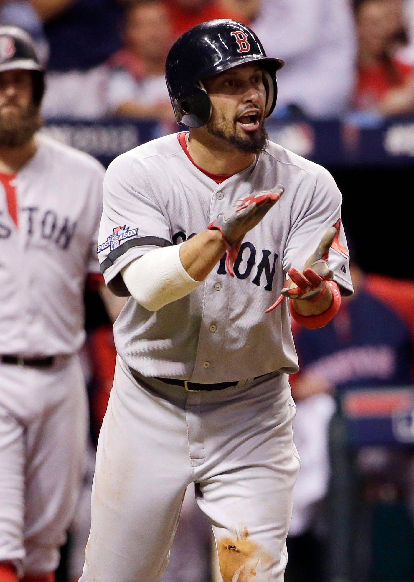 Boston's Shane Victorino applauds teammate David Ortiz after scoring on a hit by Ortiz in the fifth inning Monday.