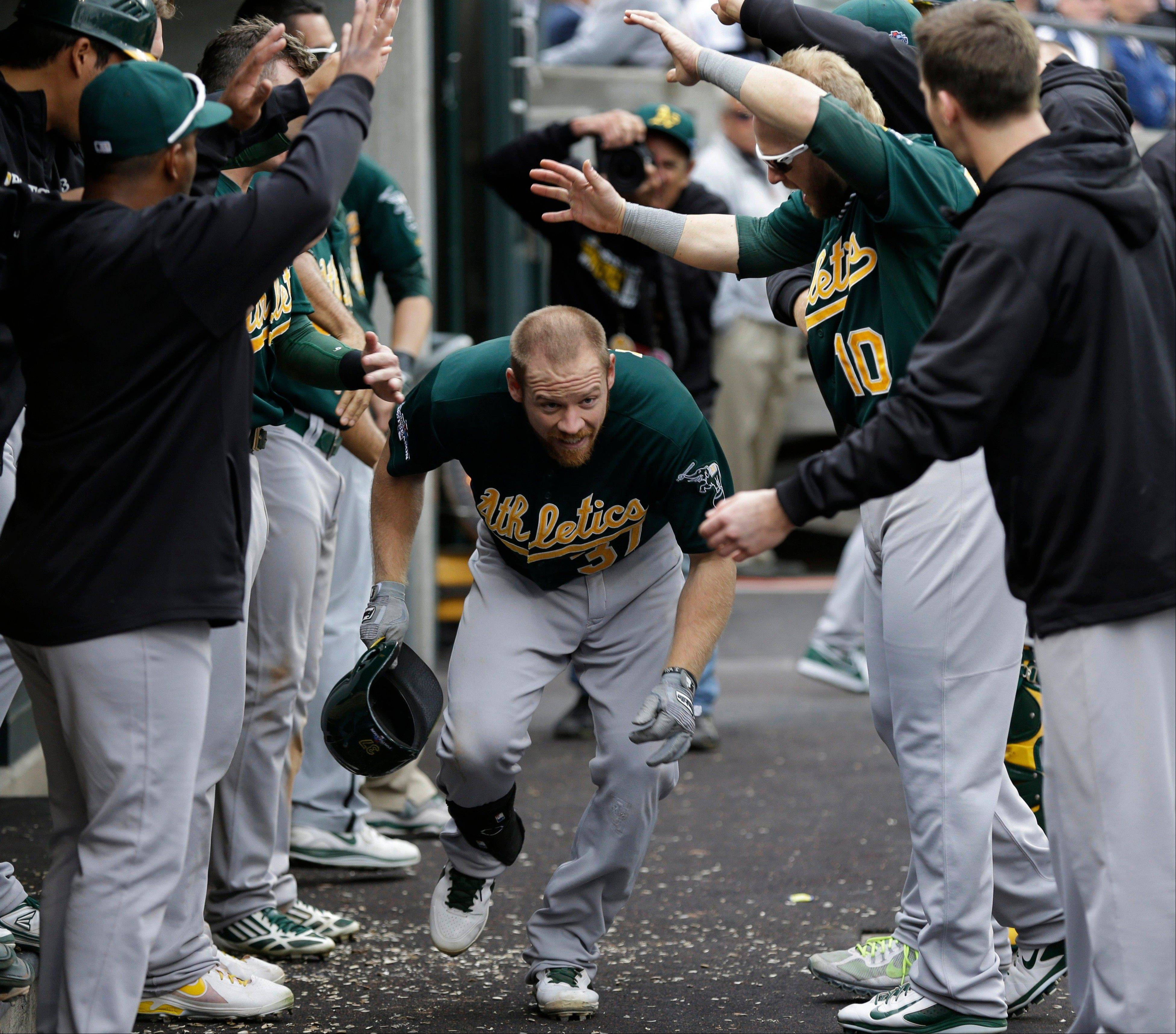 Oakland Athletics' Brandon Moss is cheered by teammates after his solo home run during the fifth inning of Game 3 Monday against the Detroit Tigers.