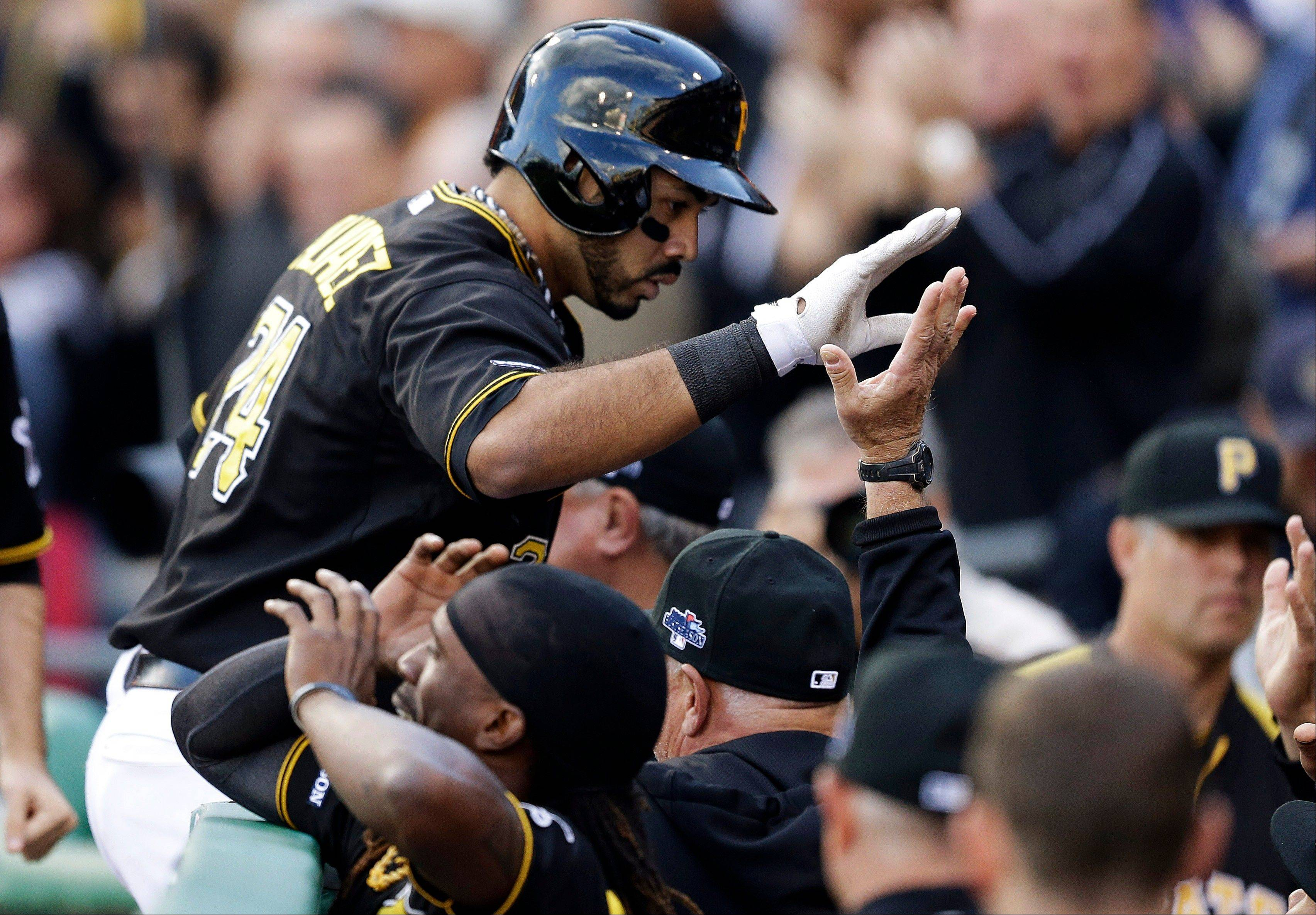 Pittsburgh Pirates' Pedro Alvarez celebrates with teammates as he returns to the dugout after his solo home run off St. Louis Cardinals pitcher Michael Wacha in the eighth inning Monday in Game 4 of their National League Division Series.