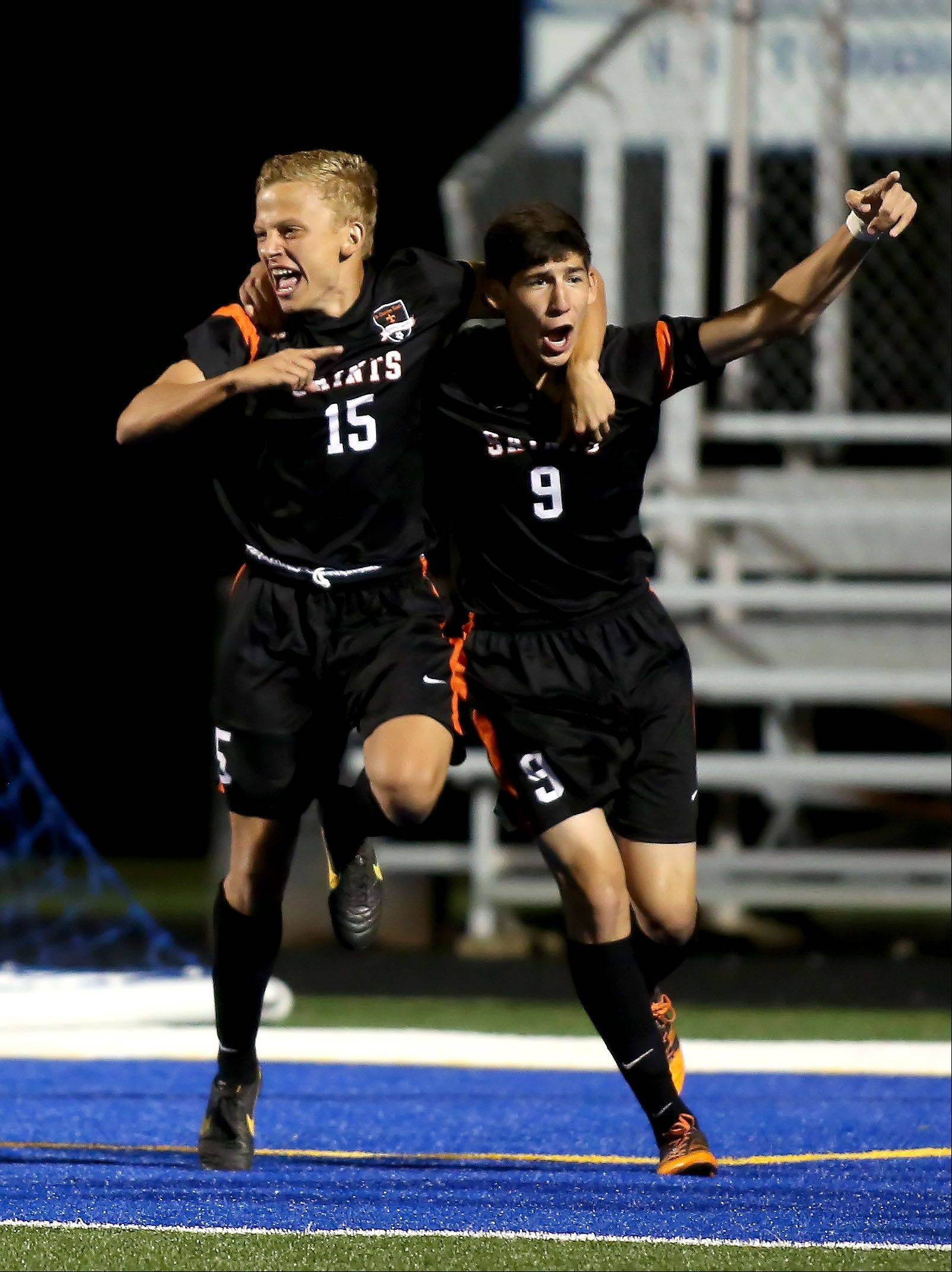 St. Charles East's Kevin Heinrich, left, and Taylor Ortizof celebrate a goal against Geneva during Tuesday's Tri-Cities boys soccer game in Geneva.
