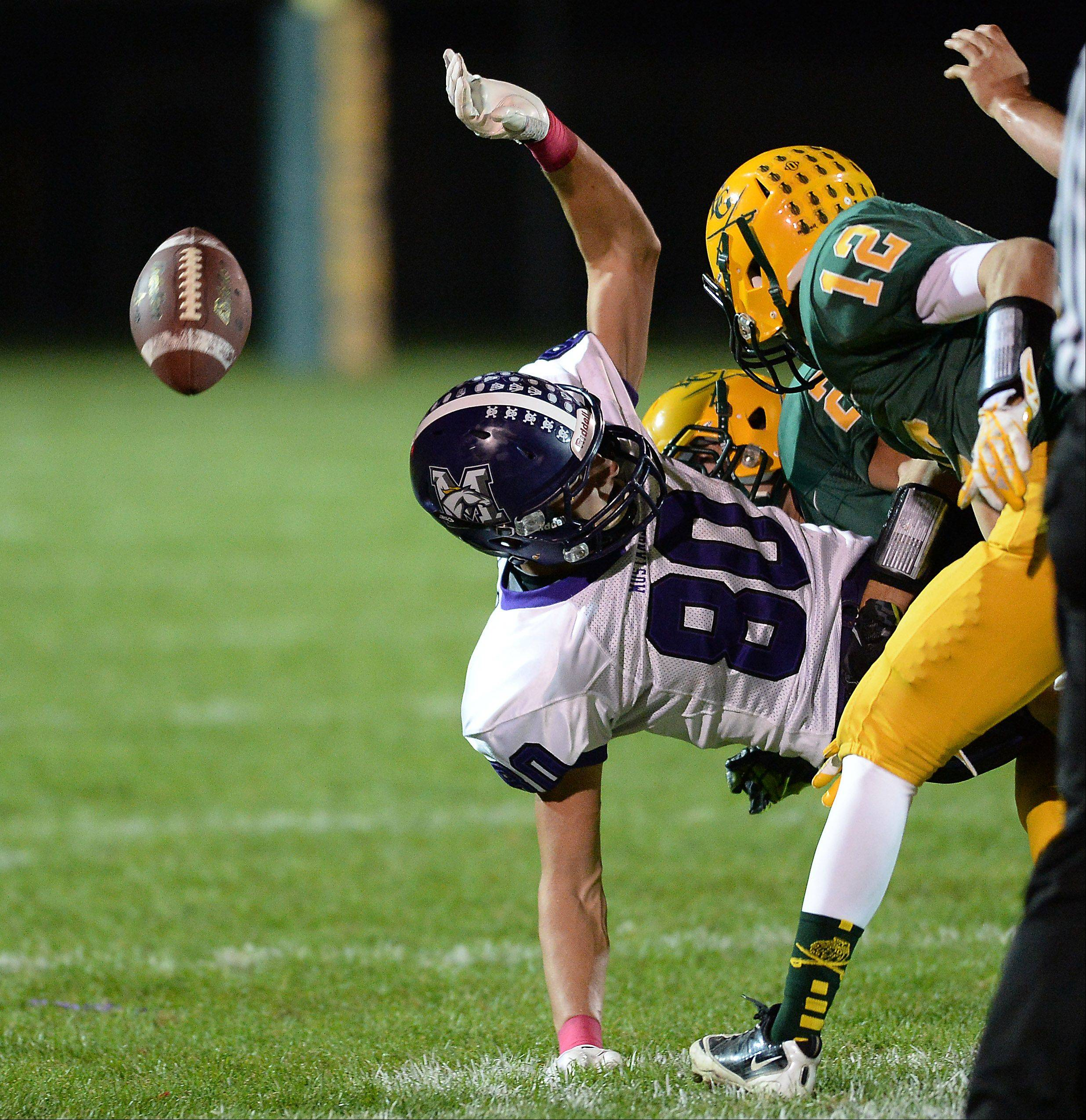Rolling Meadows' Matt Dolan gets hit by Elk Grove's Matthew Wary causing a fumble during Friday's game in Elk Grove.
