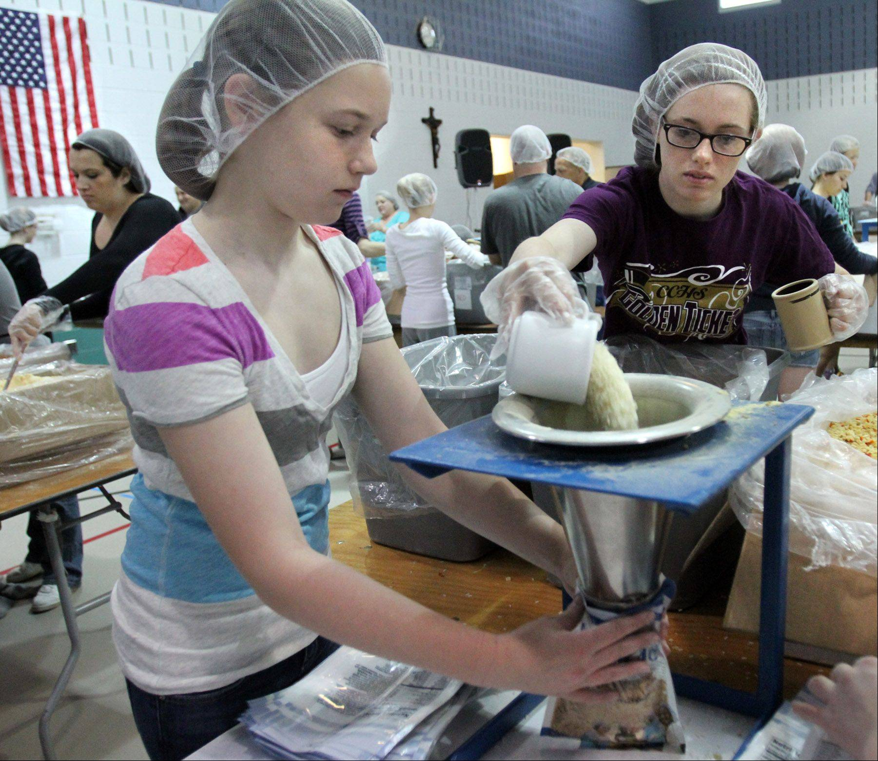 East Lake Academy sixth-grader Meg Murphy holds a food pouch as her sister, Bridie Murphy, both of Lincolnshire, pours in dry rice as Lake County volunteers pack 100,000 life-saving meals at a Feed My Starving Children event at East Lake Academy in Lake Forest.