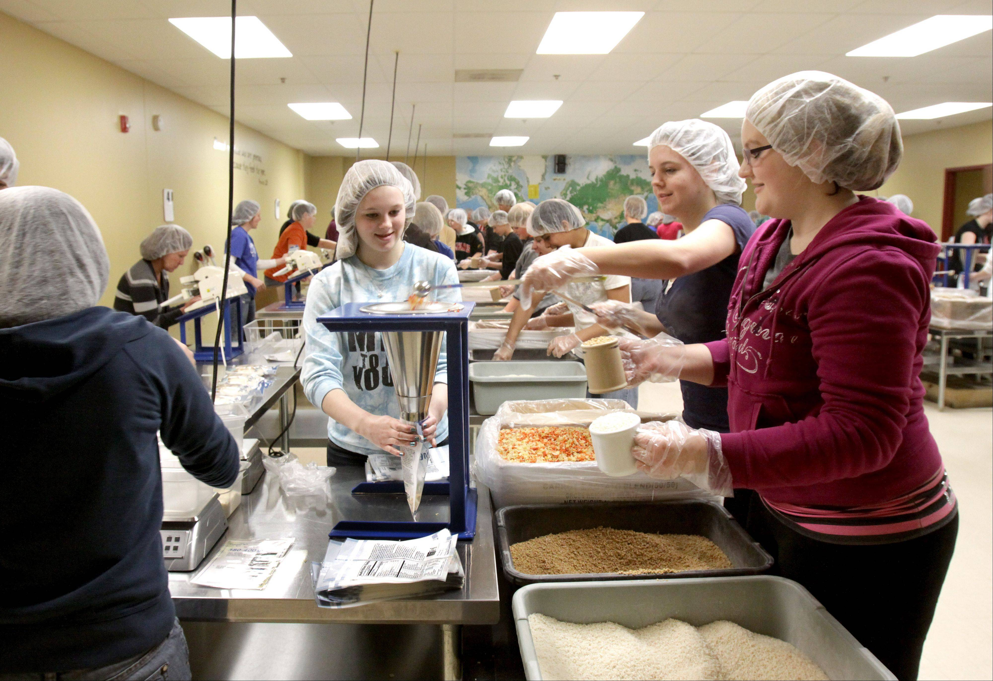 Kids from Burlington Central Middle School work at filling meal packets at Feed My Starving Children in Aurora.