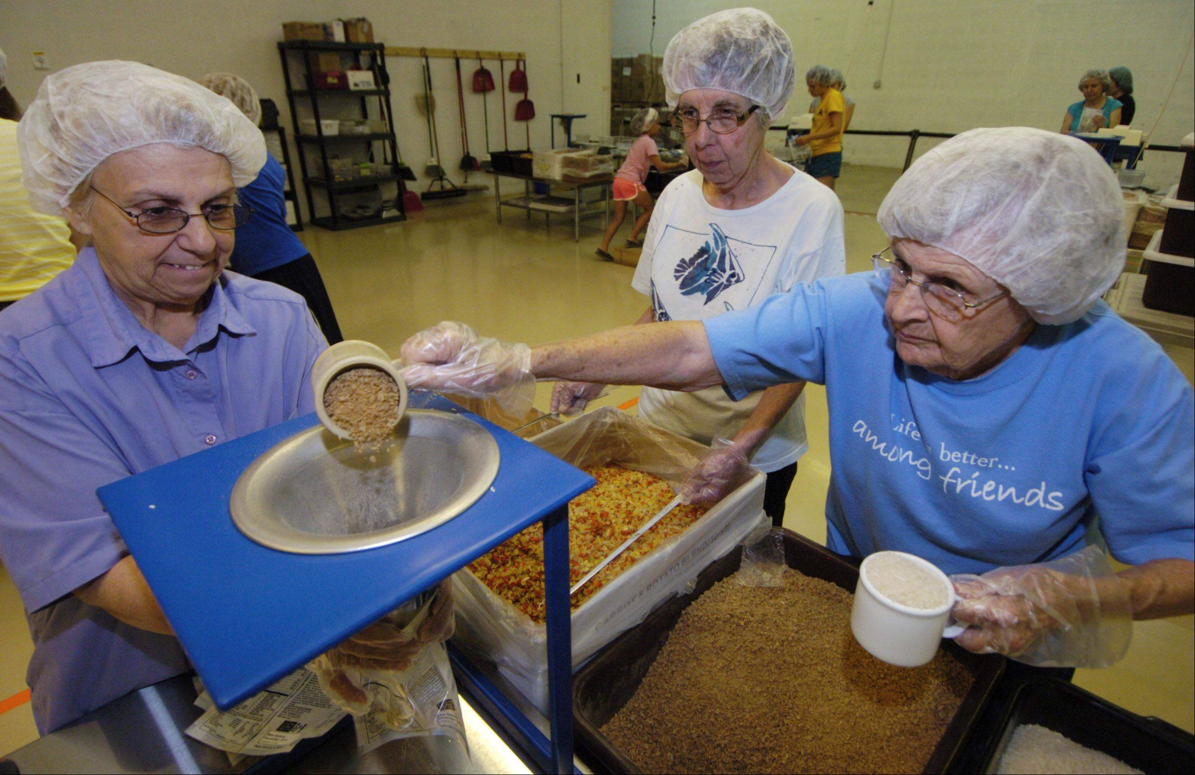 A group of seniors from Friendship Village in Schaumburg helps to pack meals at the Feed My Starving Children facility in Schaumburg.