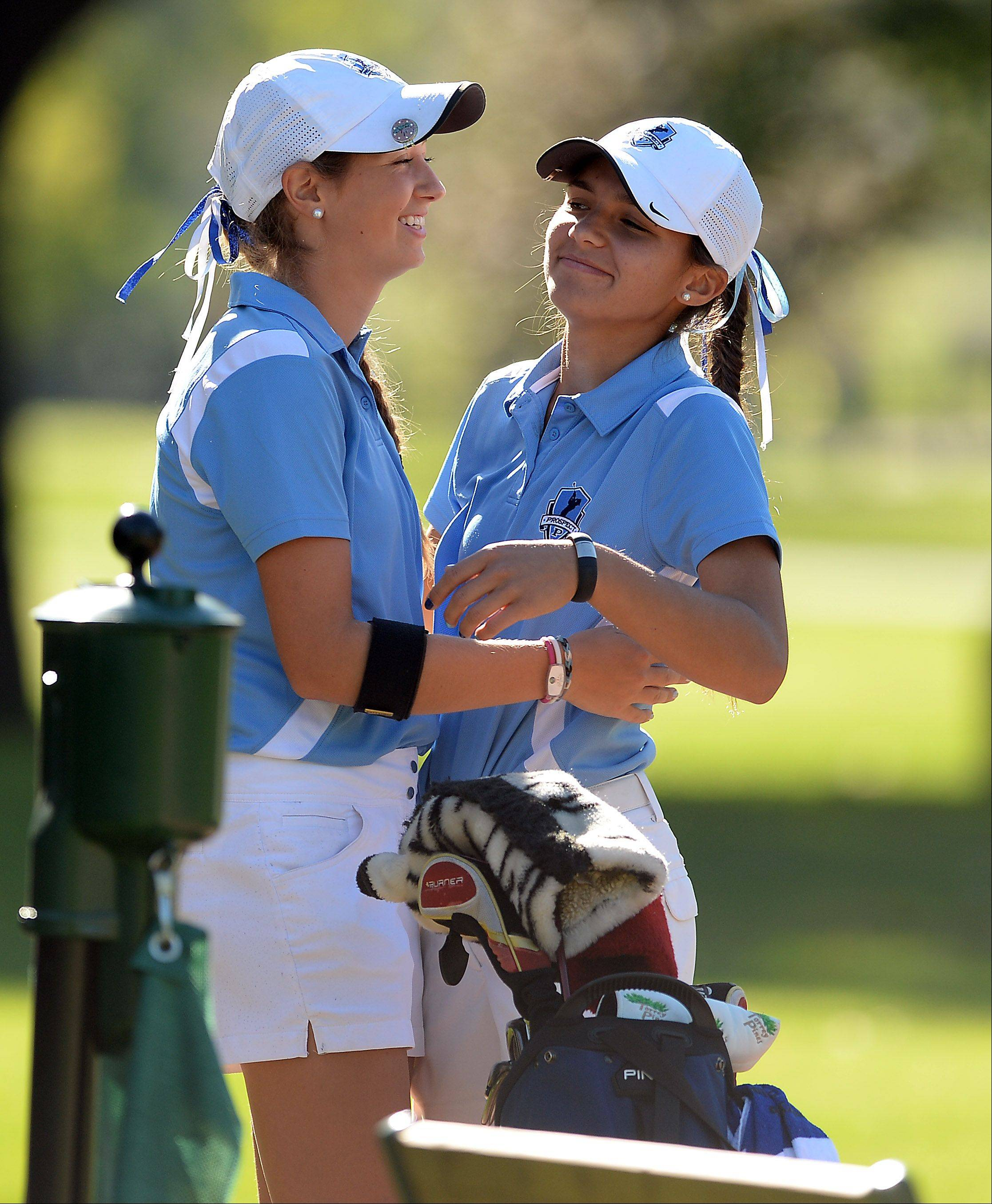 Prospect's Ally Scaccia, right, and teammate Kiley Walsh come together for a hug before the start of the girls golf regional at Mt. Prospect Golf Club on Wednesday.