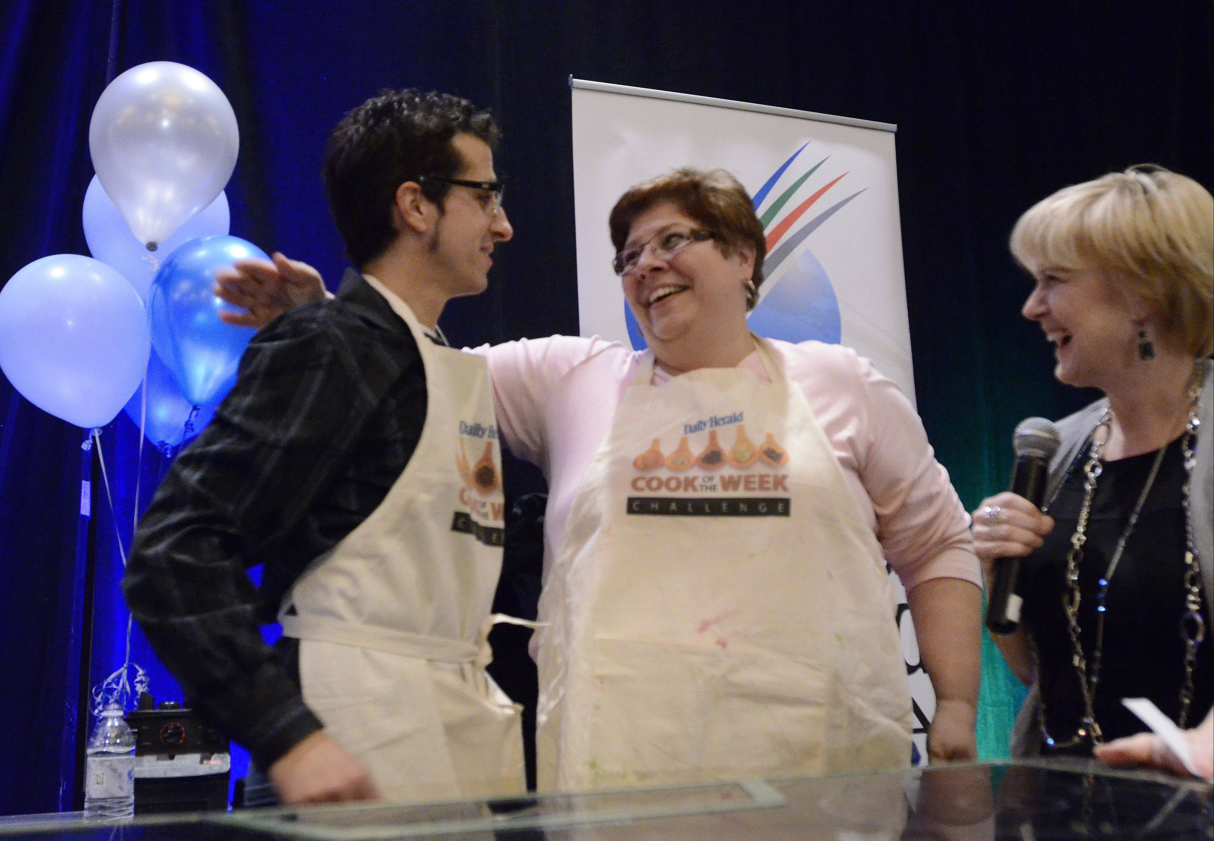 Cook of the Year Michael Pennisi gets a pat on the back from runner-up Louann Zundel during the 2012's Cook of the Week Challenge Cook-off.