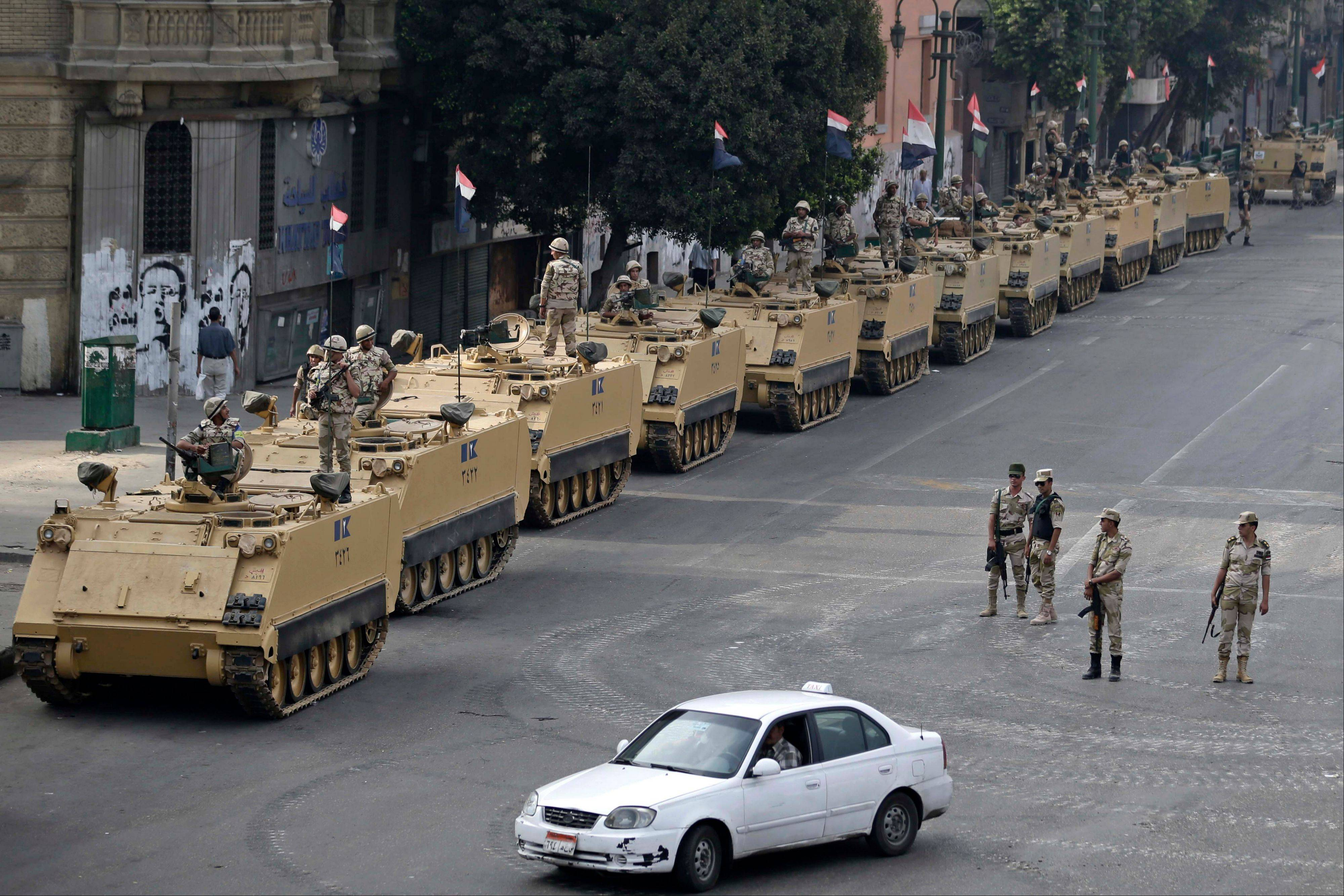 Egyptian army soldiers take positions on top of and next to armored vehicles to guard an entrance to Tahrir Square in Cairo during disturbances in August. U.S. officials said Wednesday the Obama administration is poised to slash hundreds of millions of dollars in military and economic assistance to Egypt.