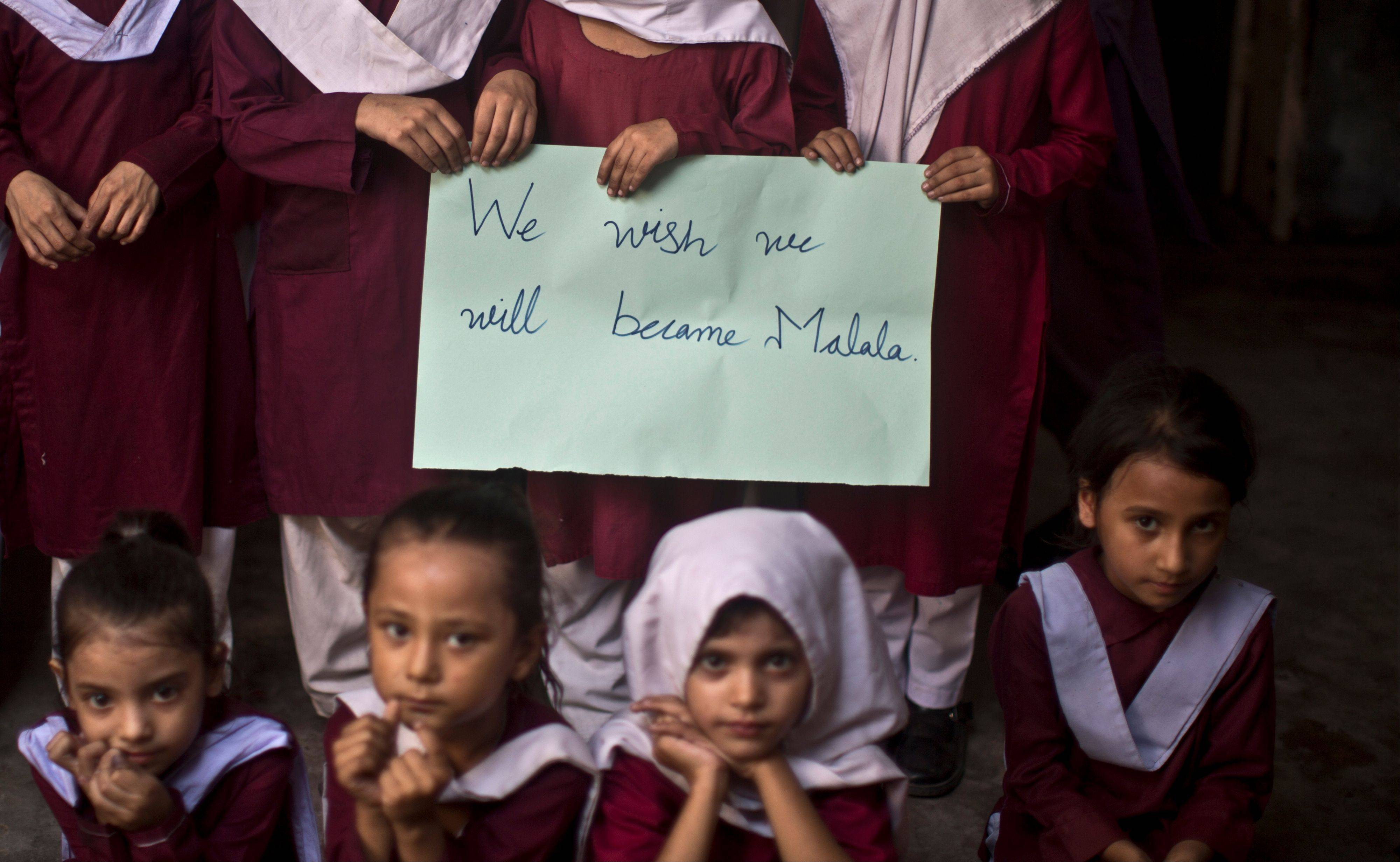 Pakistani school children hold a hand-written sign during a special class to commemorate the anniversary of Malala Yousufzai's shooting by Taliban, at a school in Rawalpindi, Pakistan, Wednesday.