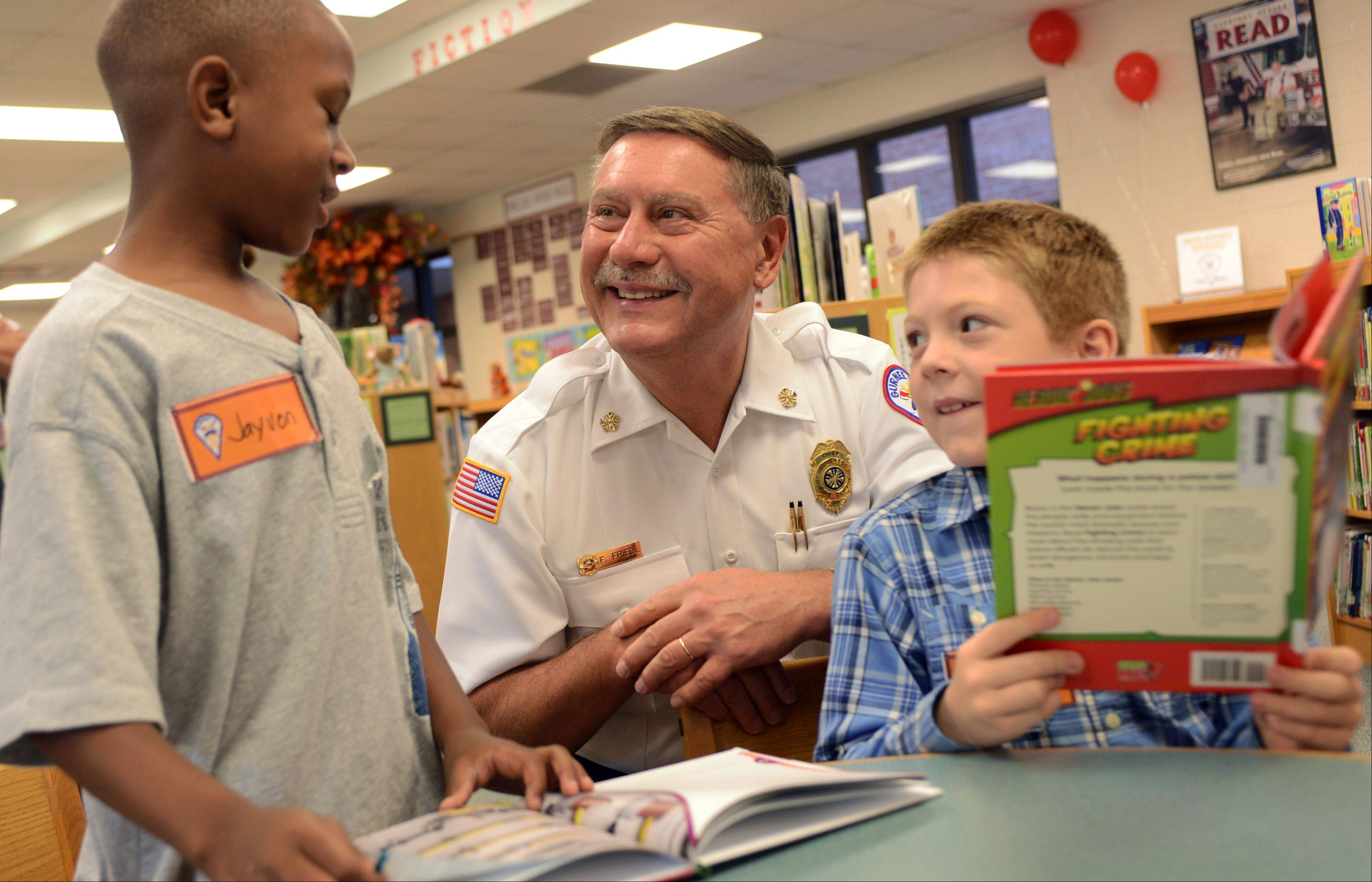 Gurnee Fire Chief Fred N. Friedl, center, looks over fire safety books with Spaulding Elementary School second grade students Jayvon Scott, left, and Cole Harmon ON Wednesday in Gurnee. Thirteen libraries served by the fire department received books and DVDs through a grant received by the department.