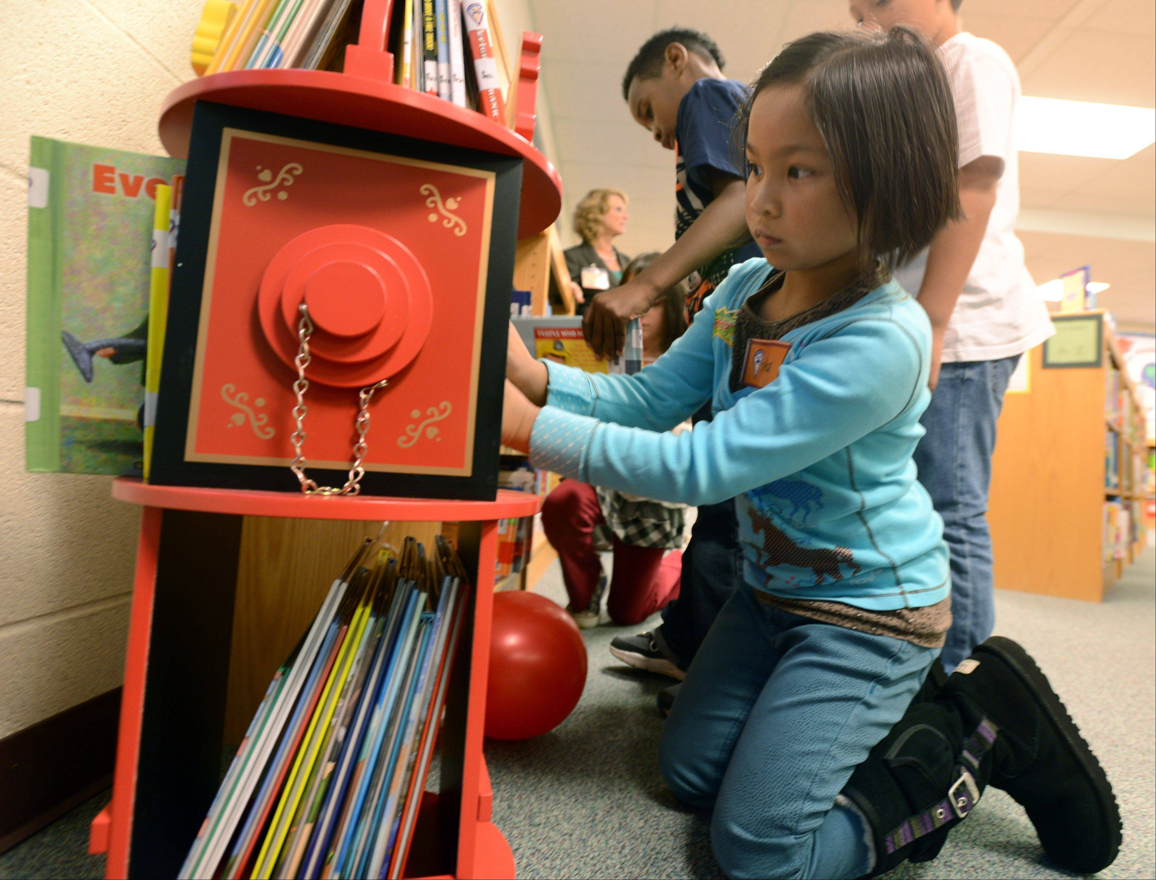 Spaulding Elementary School second-grader Erika Relayson looks over books on a fire hydrant shelf Wednesday after the display was unveiled by local fire and village officials.