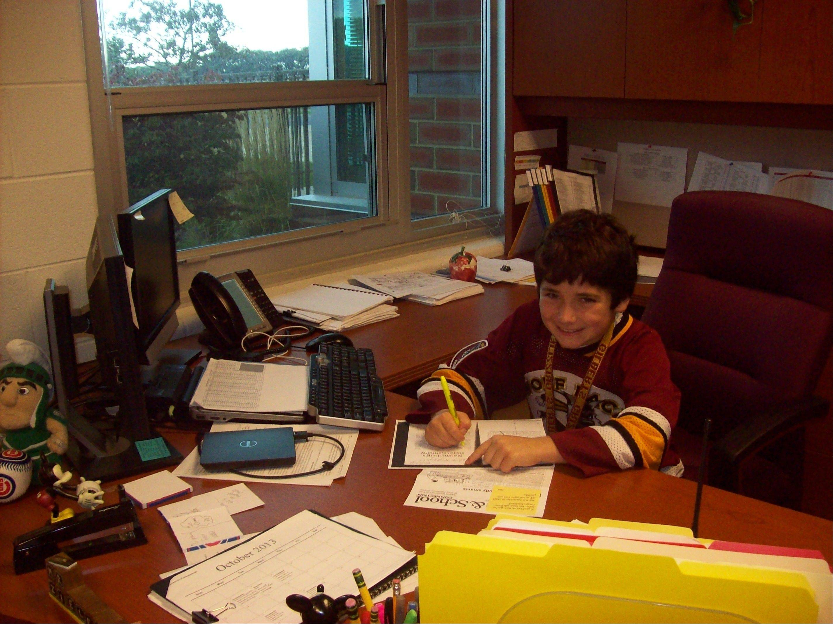 """Principal for a day"" Vincenzo Pellegrino, a Gilberts Elementary student, on the job doing paperwork."