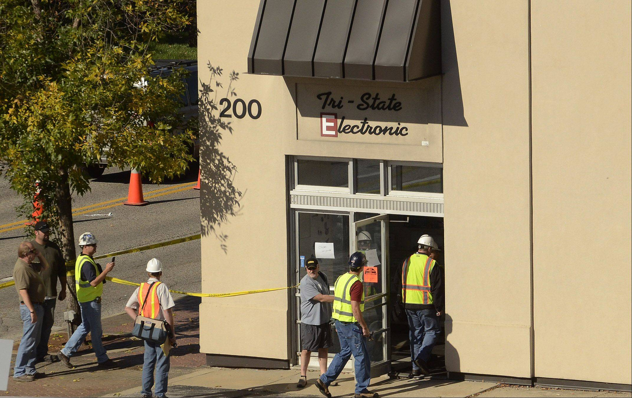 Workers enter Tri-State Electronics in Mount Prospect to inspect structural damage due to a roof collapse.