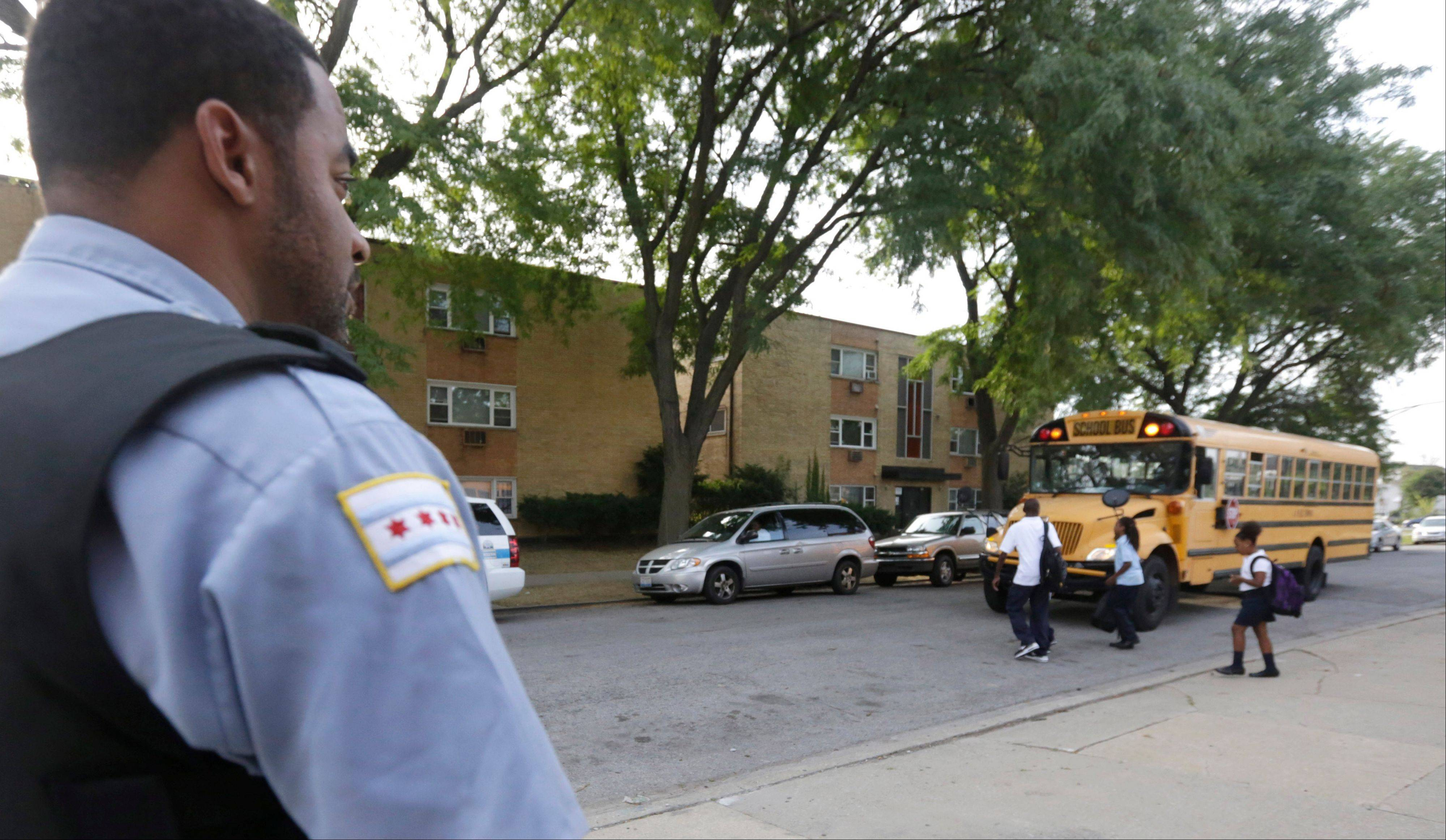 A police officer watches children board a school bus at Gresham Elementary School on the first day of classes in Chicago in late August.