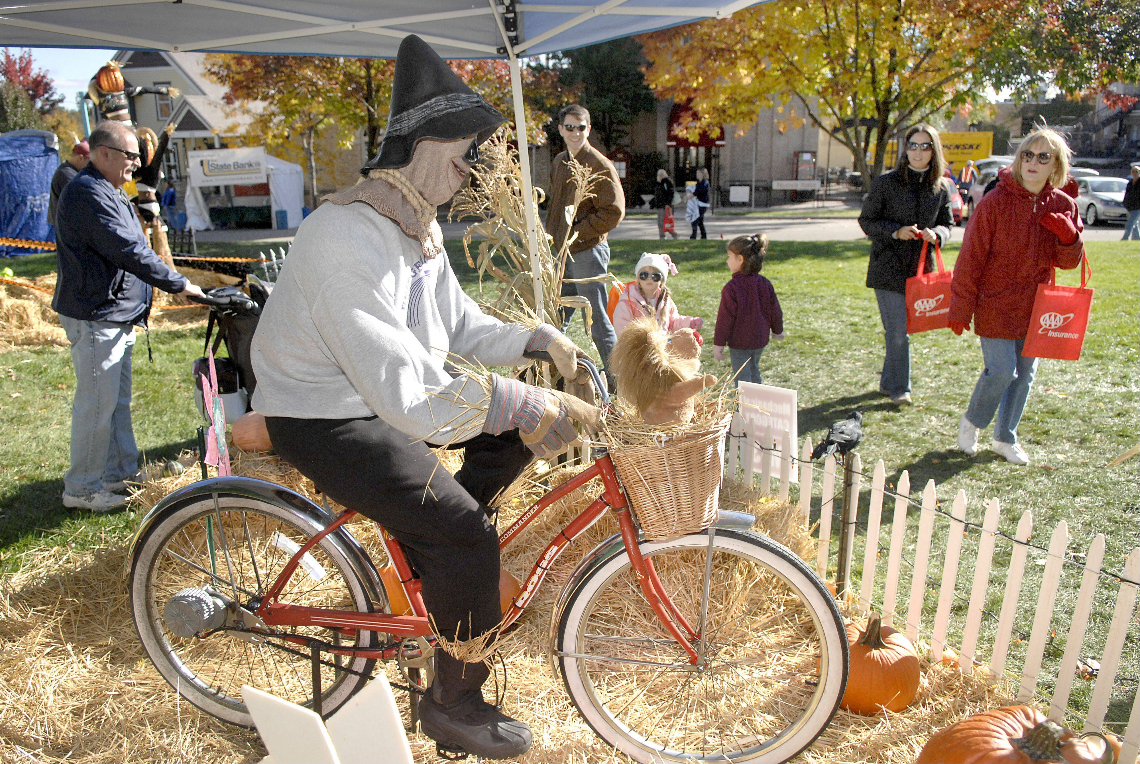The Scarecrow from the Wizard of Oz rides a bike in the mechanical category entered by Bridges Montessori Academy at a previous St. Charles Scarecrow Festival.