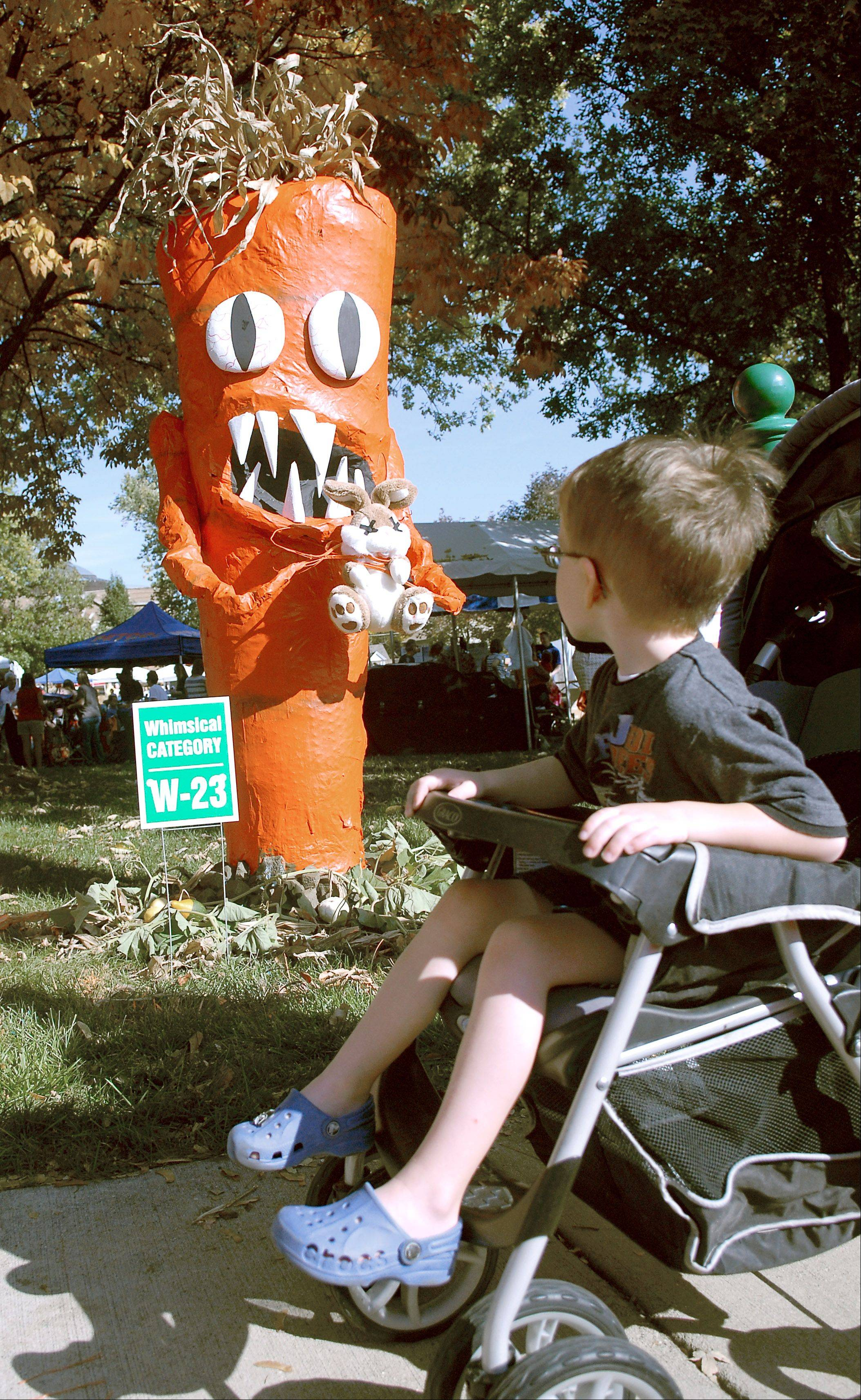Spencer McCall, 4, of Campton Hills has a great seat while viewing entries in the whimsical category at a previous St. Charles Scarecrow Fest in Lincoln Park.