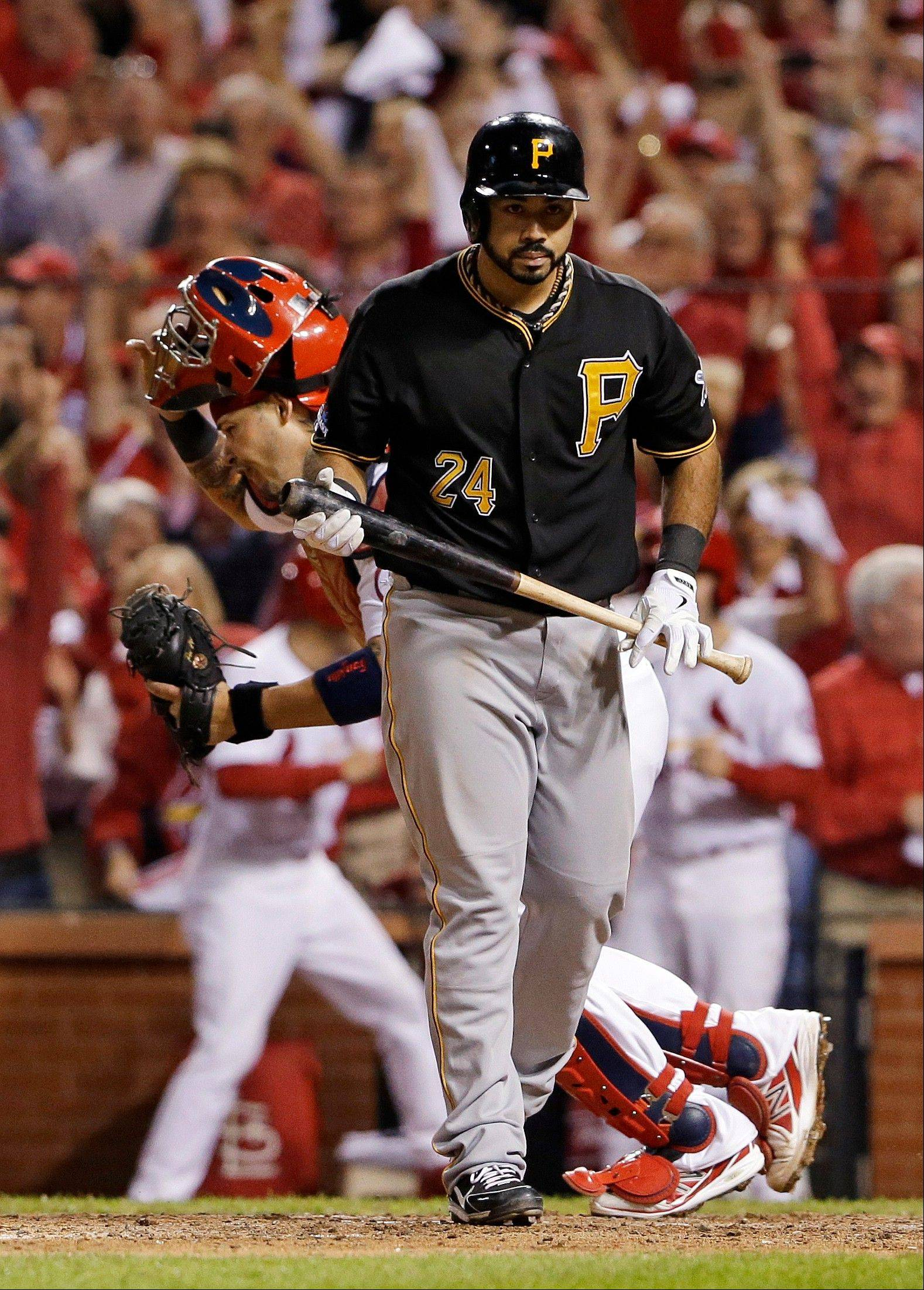 Cardinals catcher Yadier Molina, right, celebrates after the Pirates' Pedro Alvarez, left, struck out in the top of the ninth inning to end Game 5.