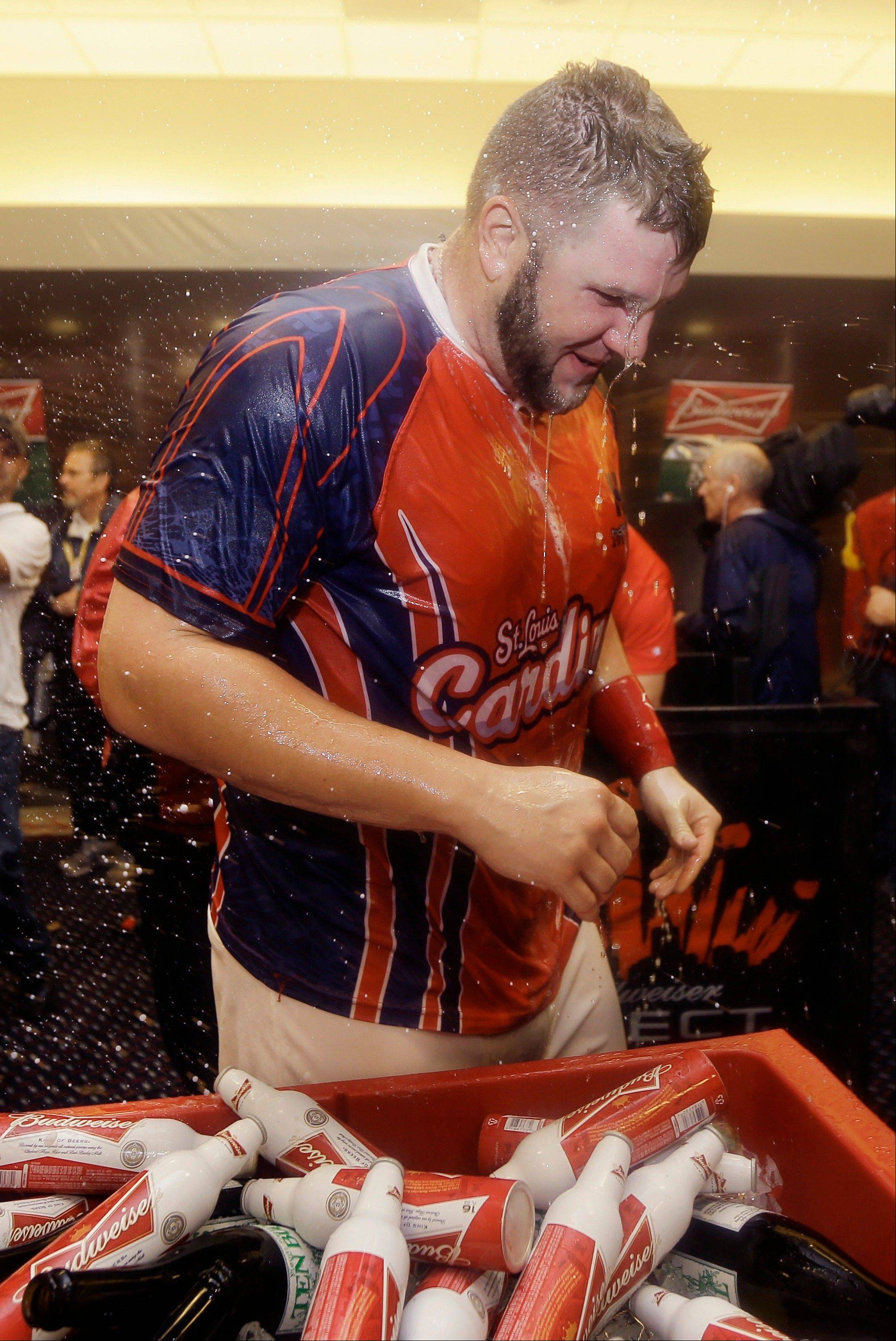 The Cardinals' Matt Adams stands in the clubhouse amid the champagne celebration after the Cardinals defeated the Pittsburgh Pirates to win their division series.