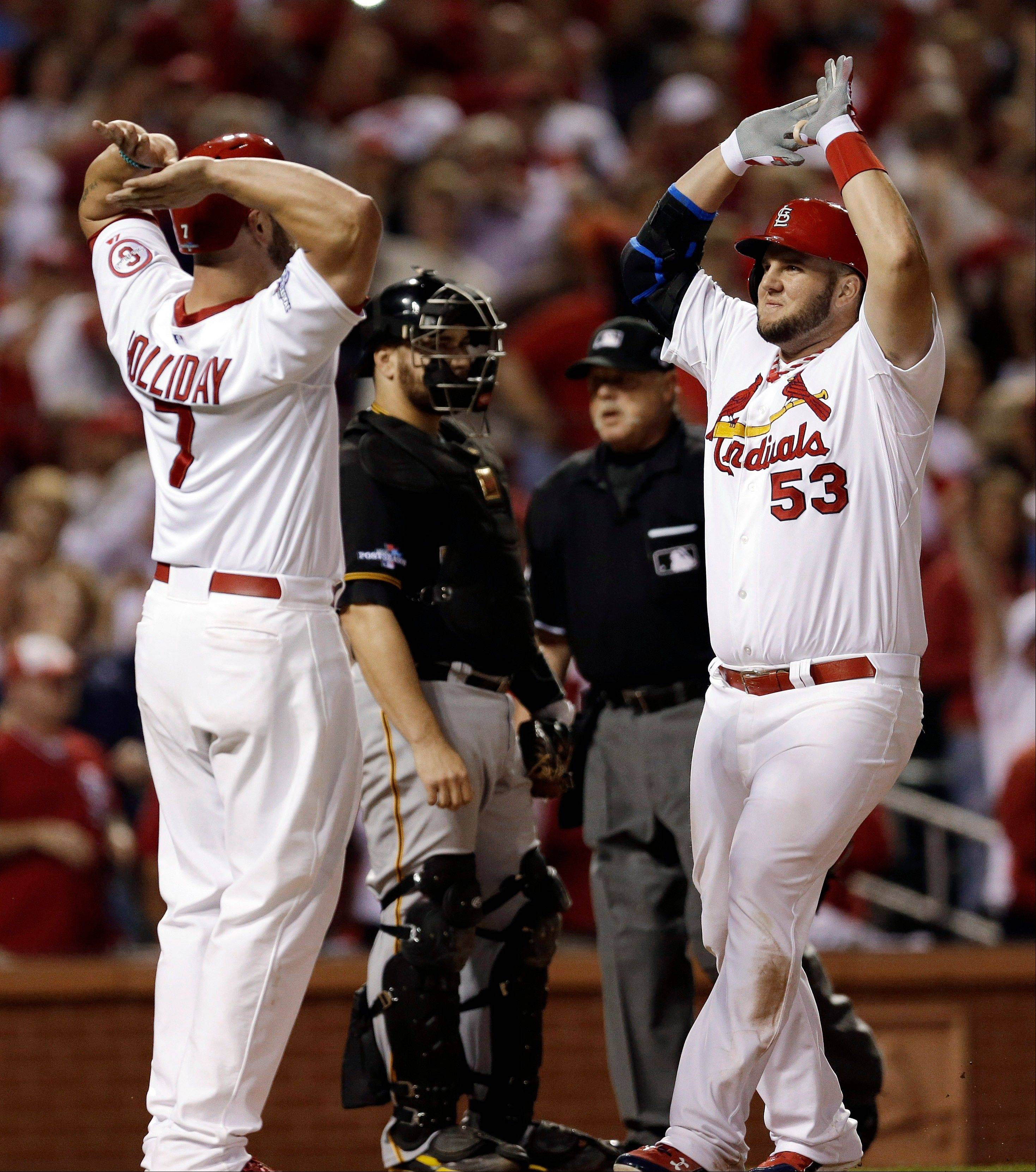 Matt Adams (53) celebrates with Matt Holliday (7) after hitting a two-run home run against the Pittsburgh Pirates in the eighth inning Wednesday in Game 5.
