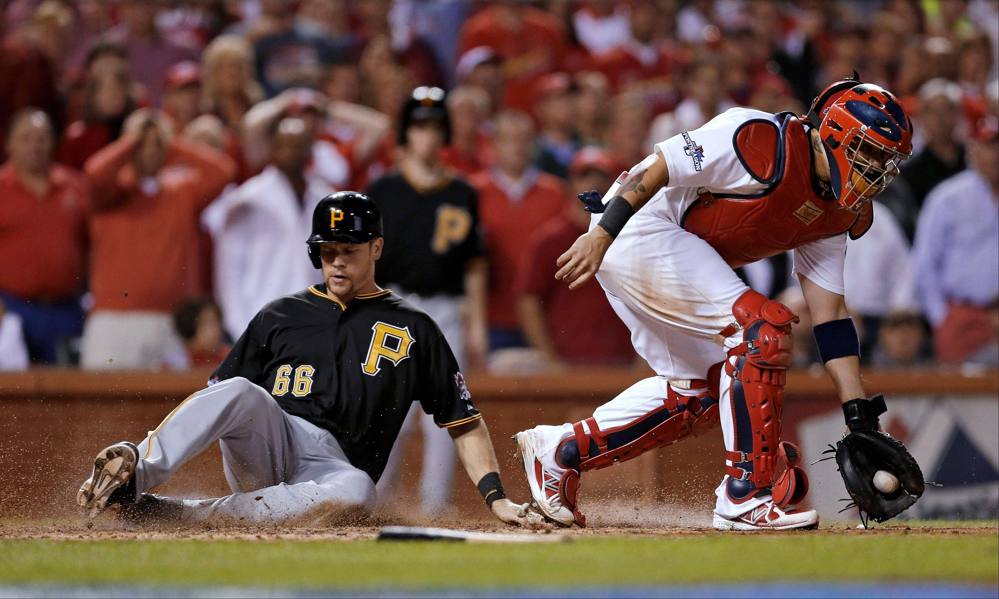 The Pirates' Justin Morneau scores on a ground ball hit by Pedro Alvarez as Cardinals catcher Yadier Molina takes the throw in the top of the seventh inning Wednesday in St. Louis.