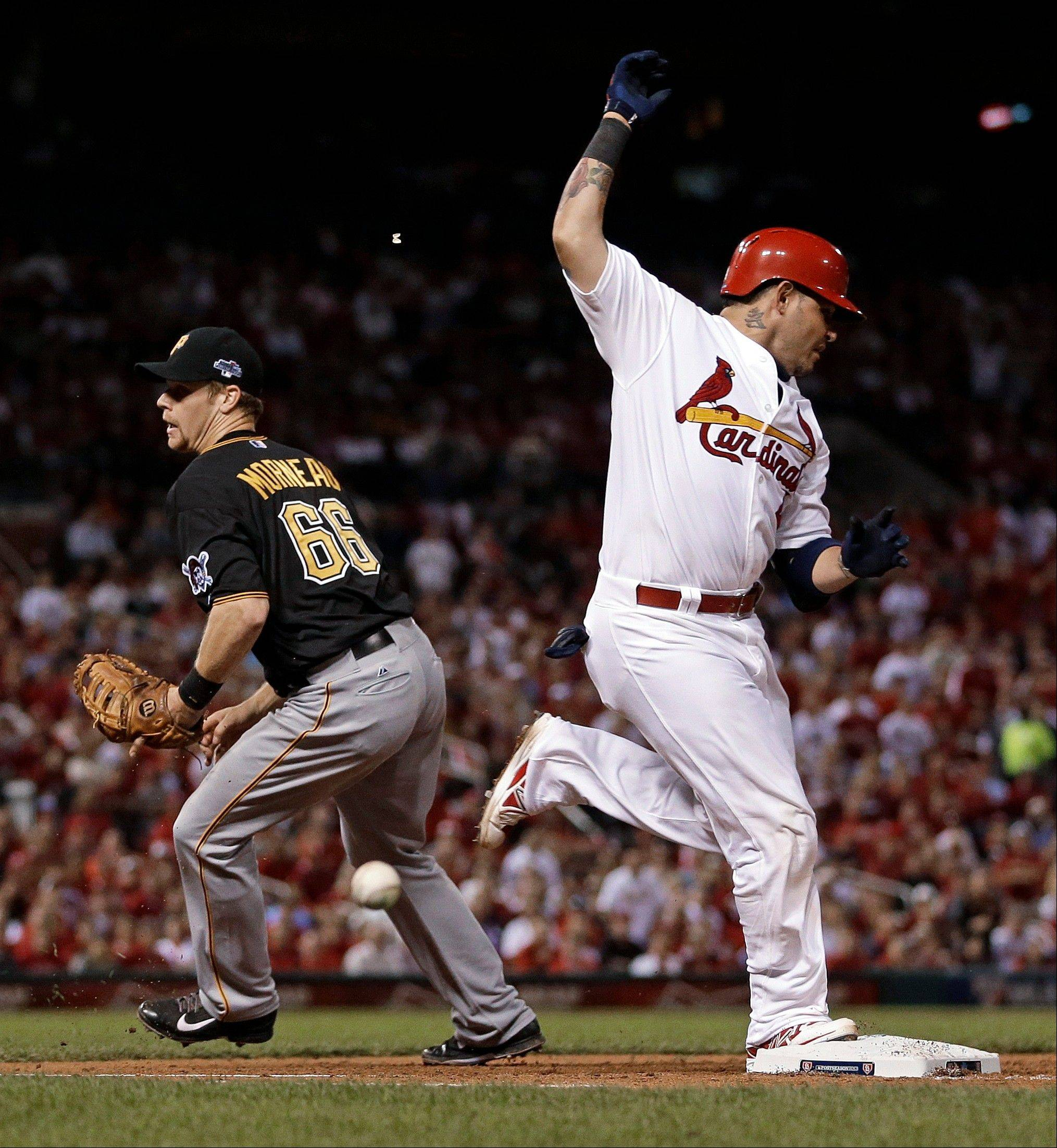 The Cardinals' Yadier Molina reaches safely as the ball gets past Pirates first baseman Justin Morneau in the fourth inning Wednesday in Game 5.